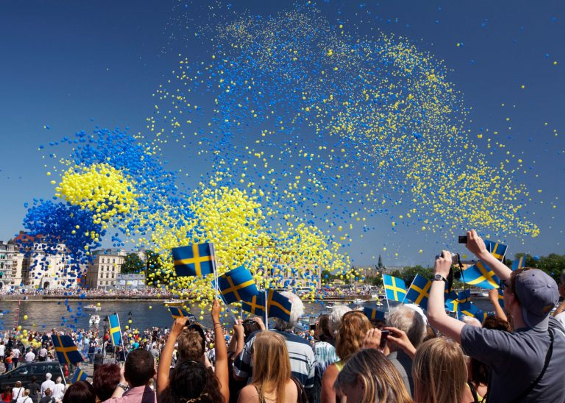 People waving Swedish flags in celebration.