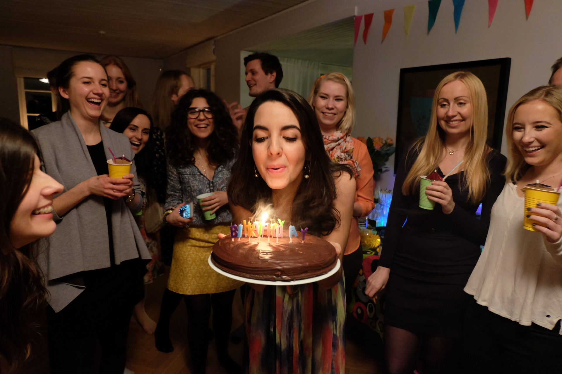Person blowing out candles on a birthday cake.