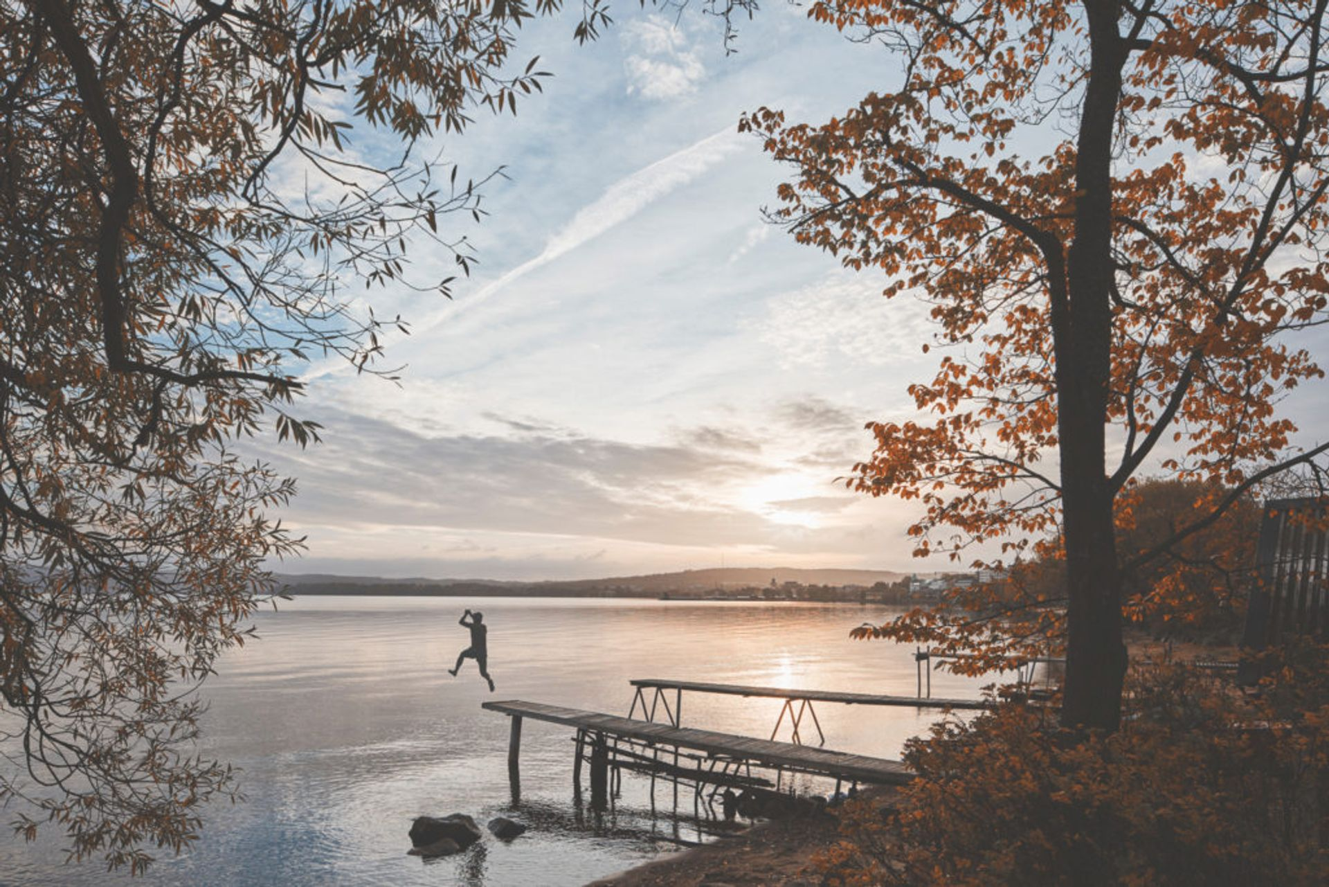 Person jumping off a wooden jetty into a lake.