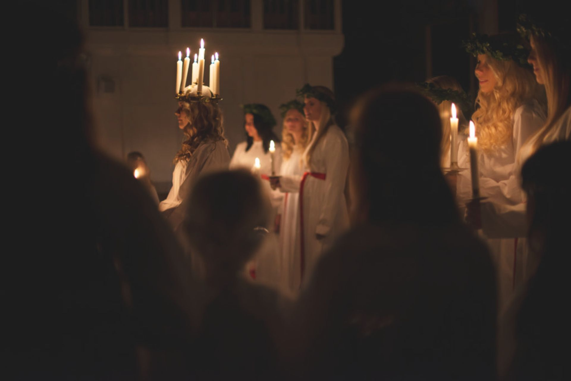 People holding candles as a part of a Lucia celebration.