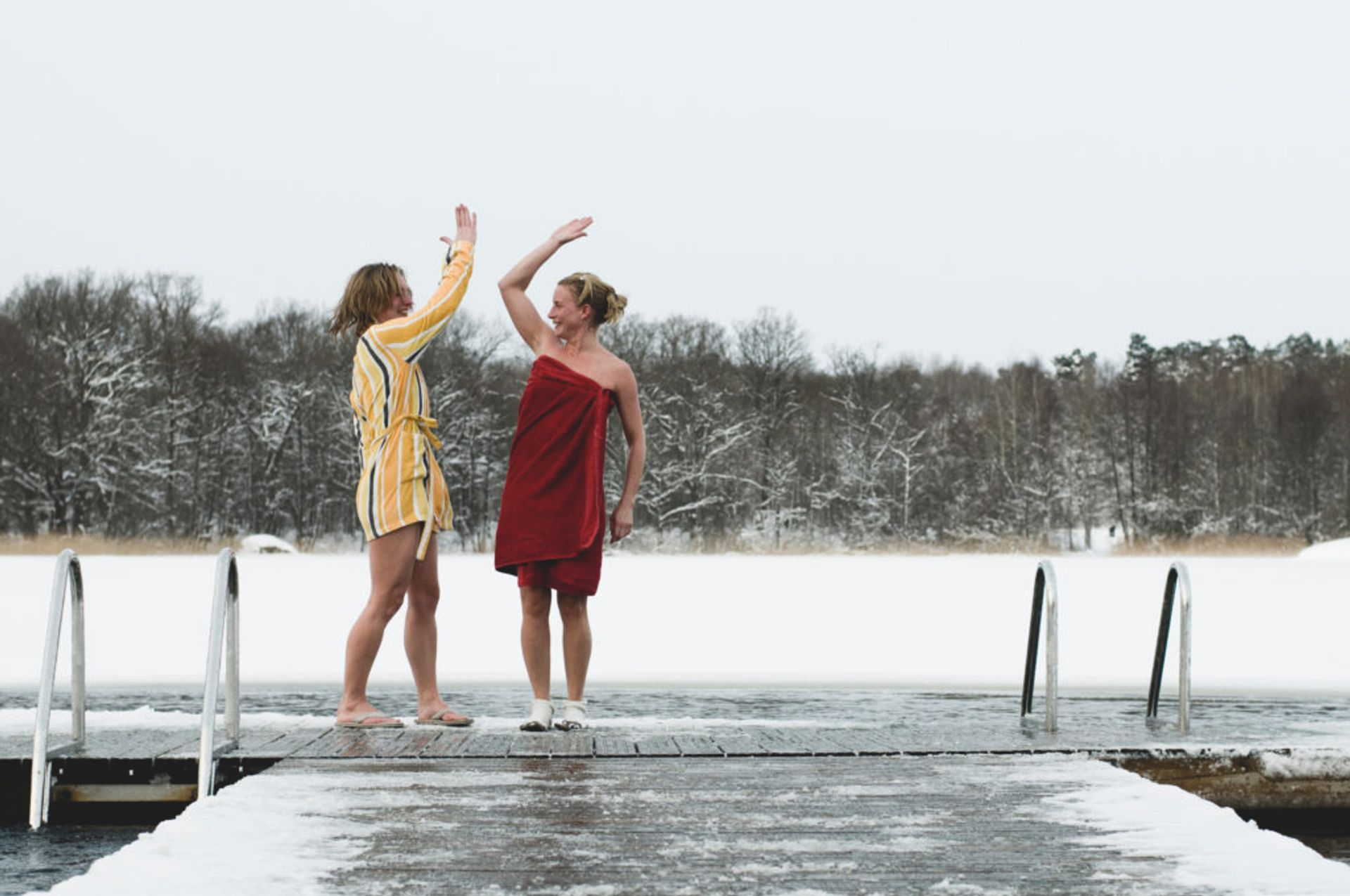 Two people standing on a snow covered jetty.