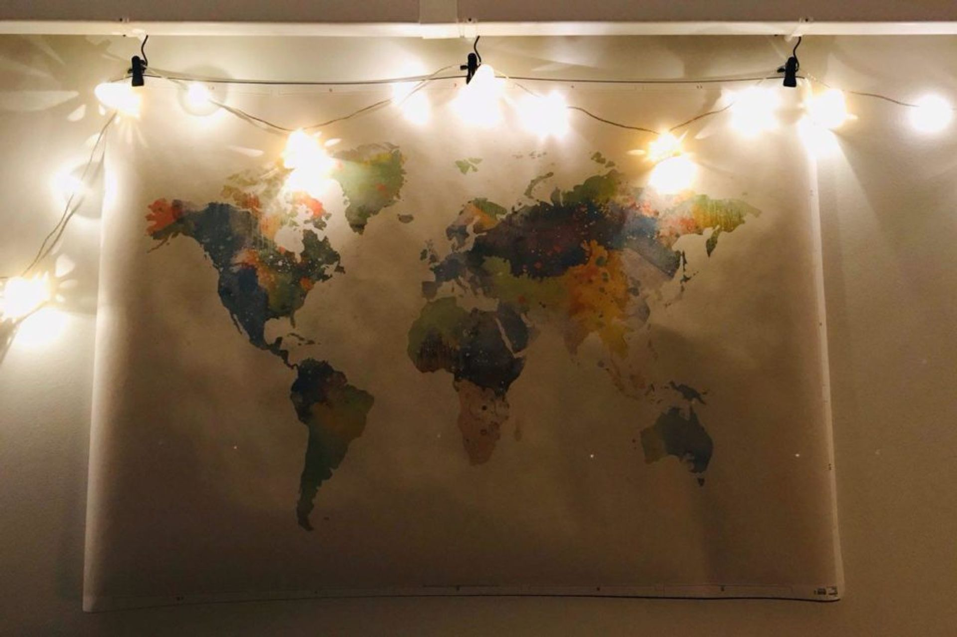 A world map hanging on a wall.
