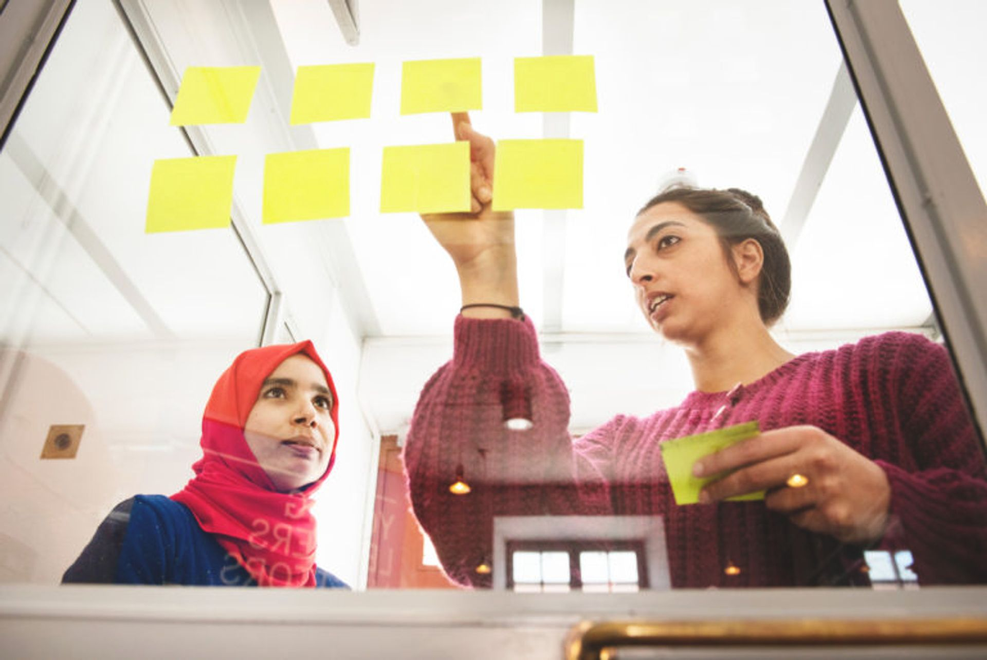 Two students working on a project with yellow post-it notes.
