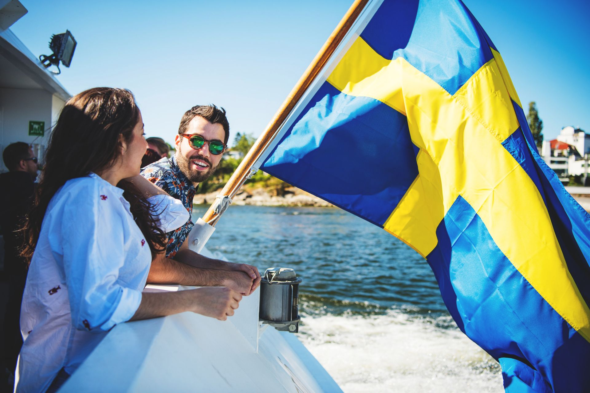Two people standing beside the Swedish flag at the back of a boat.