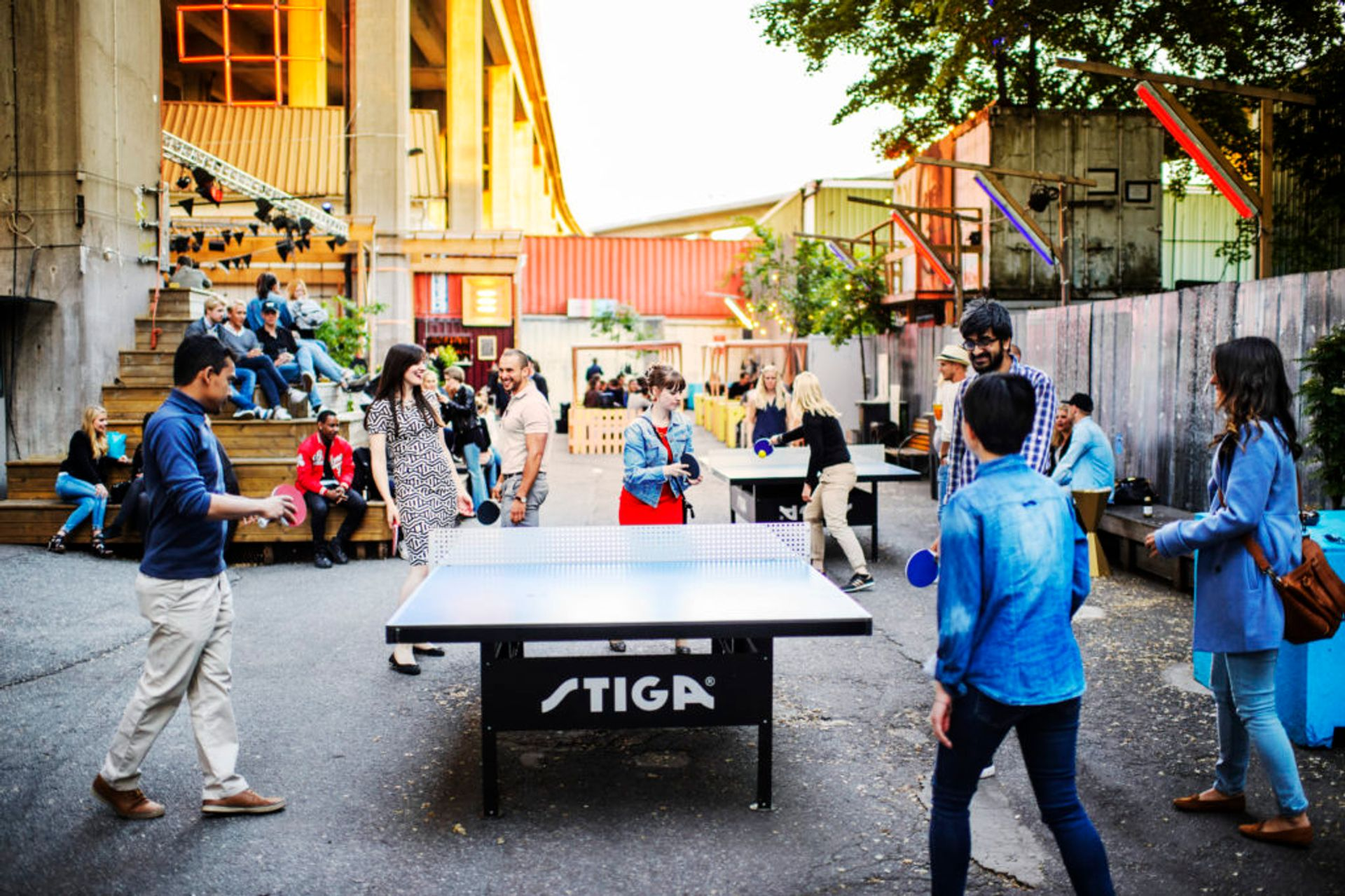 Students playing table tennis outside.
