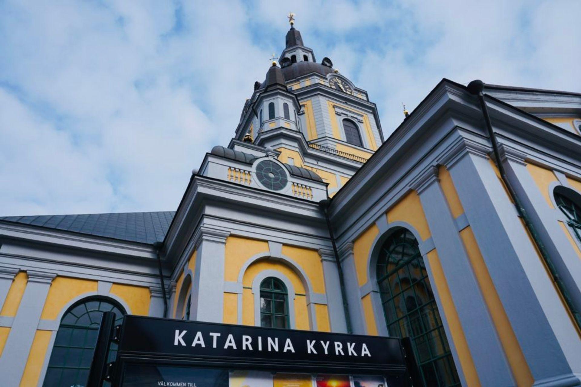 Exterior of a yellow church, sign reads 'Katarina kyrka'.