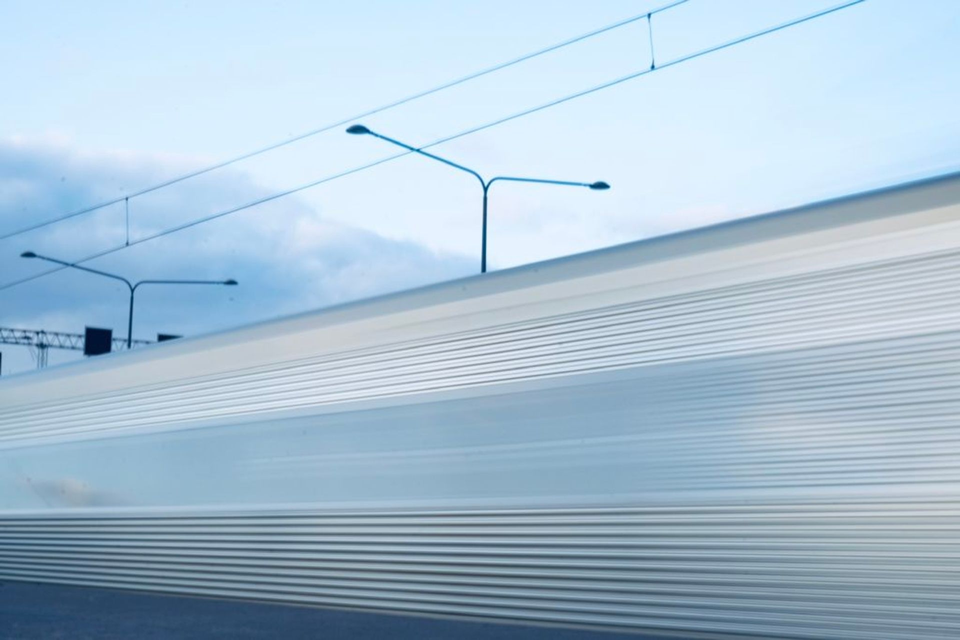 A silver train passing by quickly.