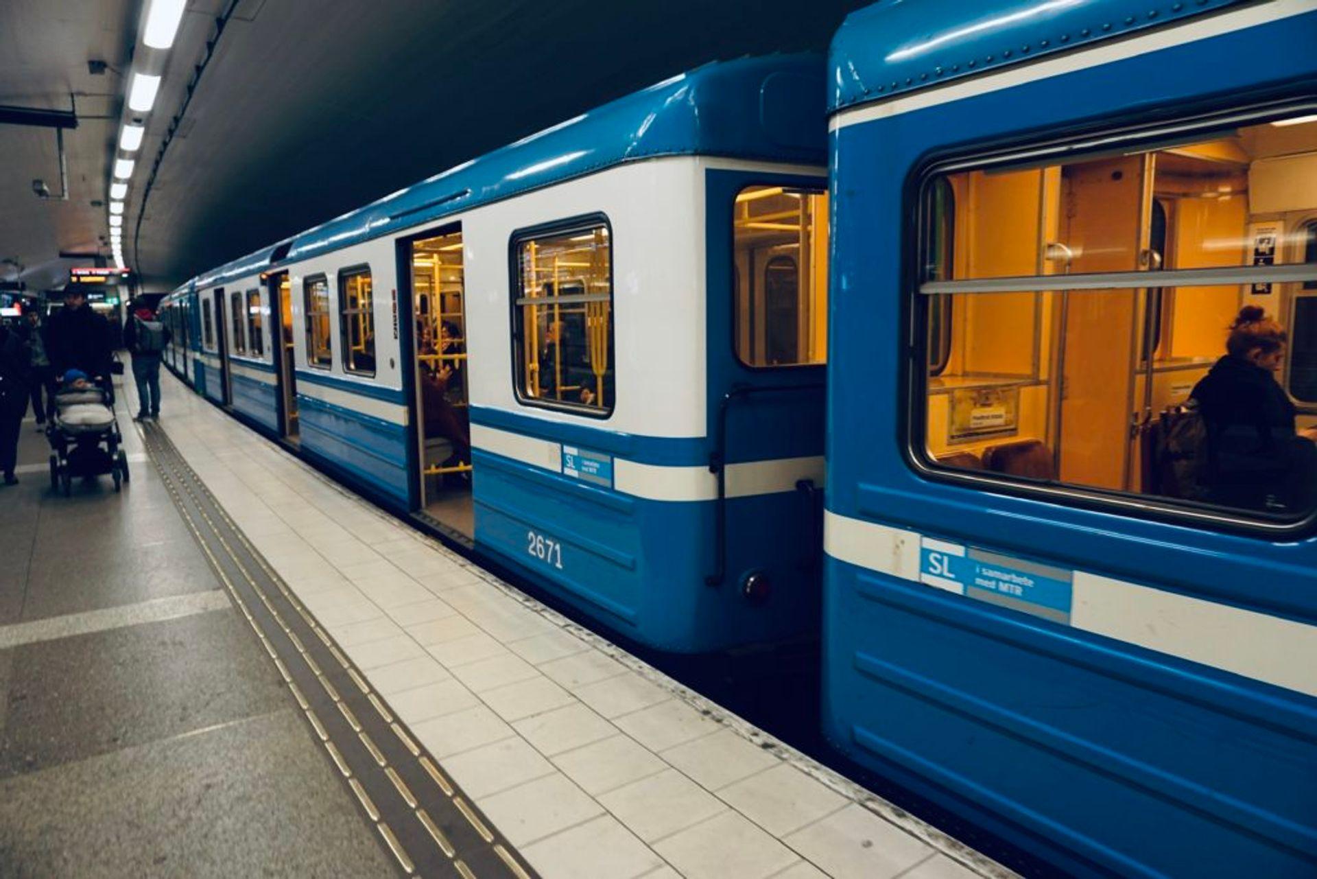 Blue metro trains waiting at a metro station.