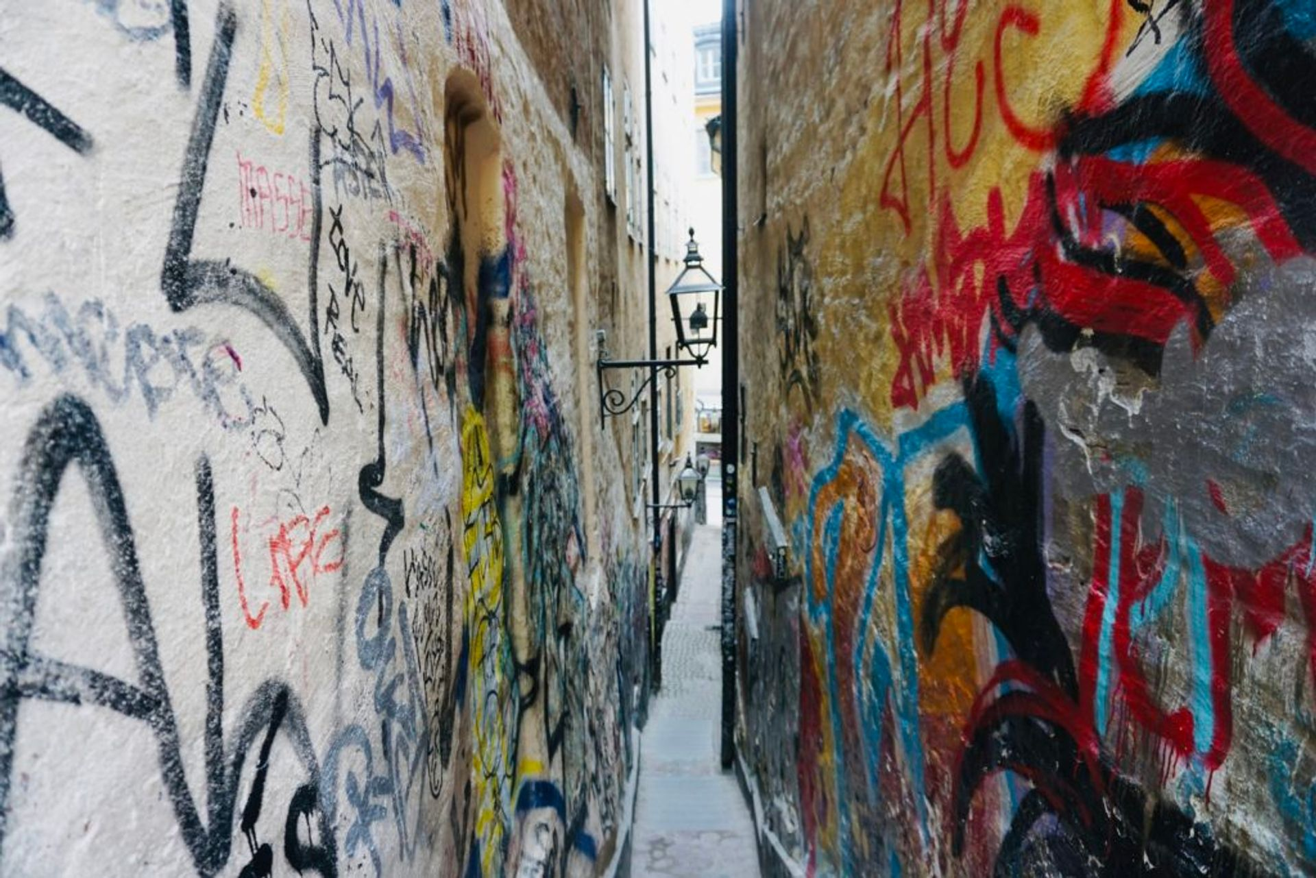 Graffiti covering walls in a narrow alley.