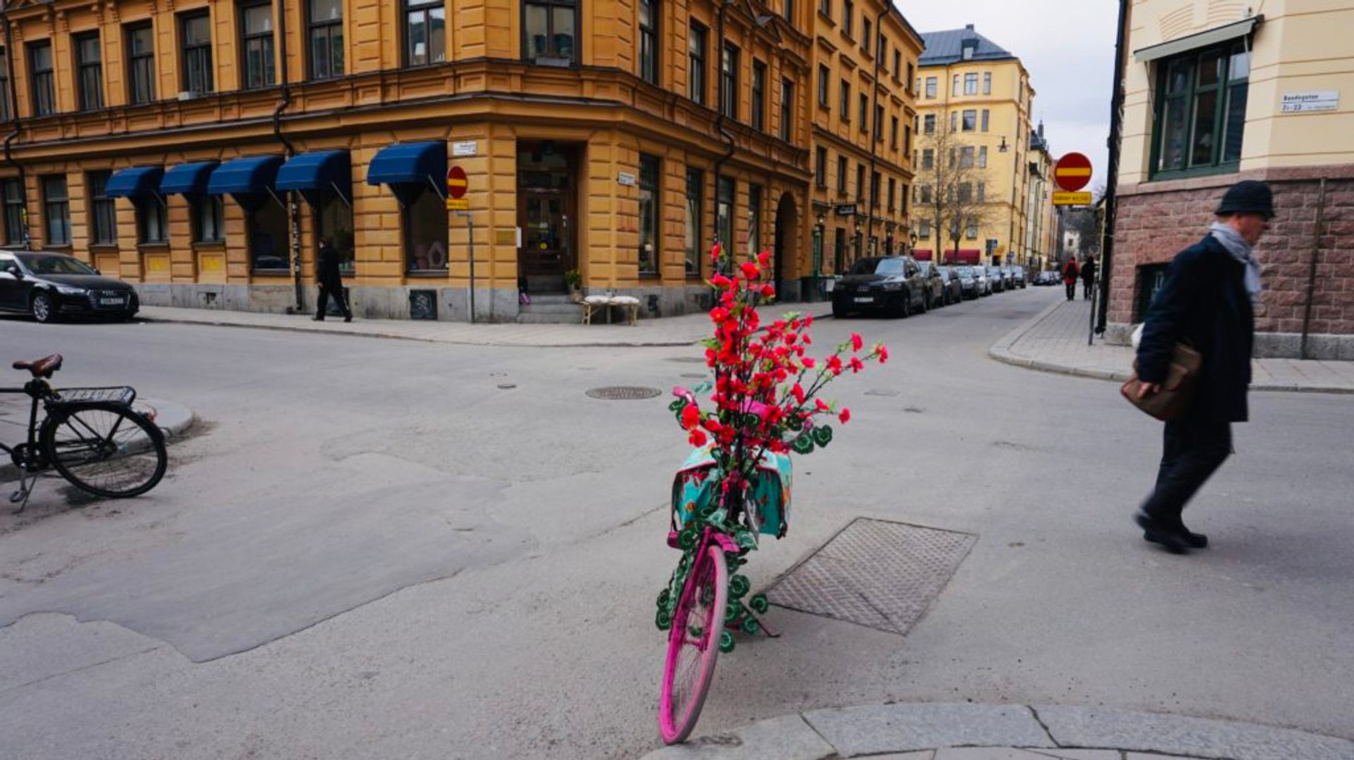 A pink bicycle parked outside a store.