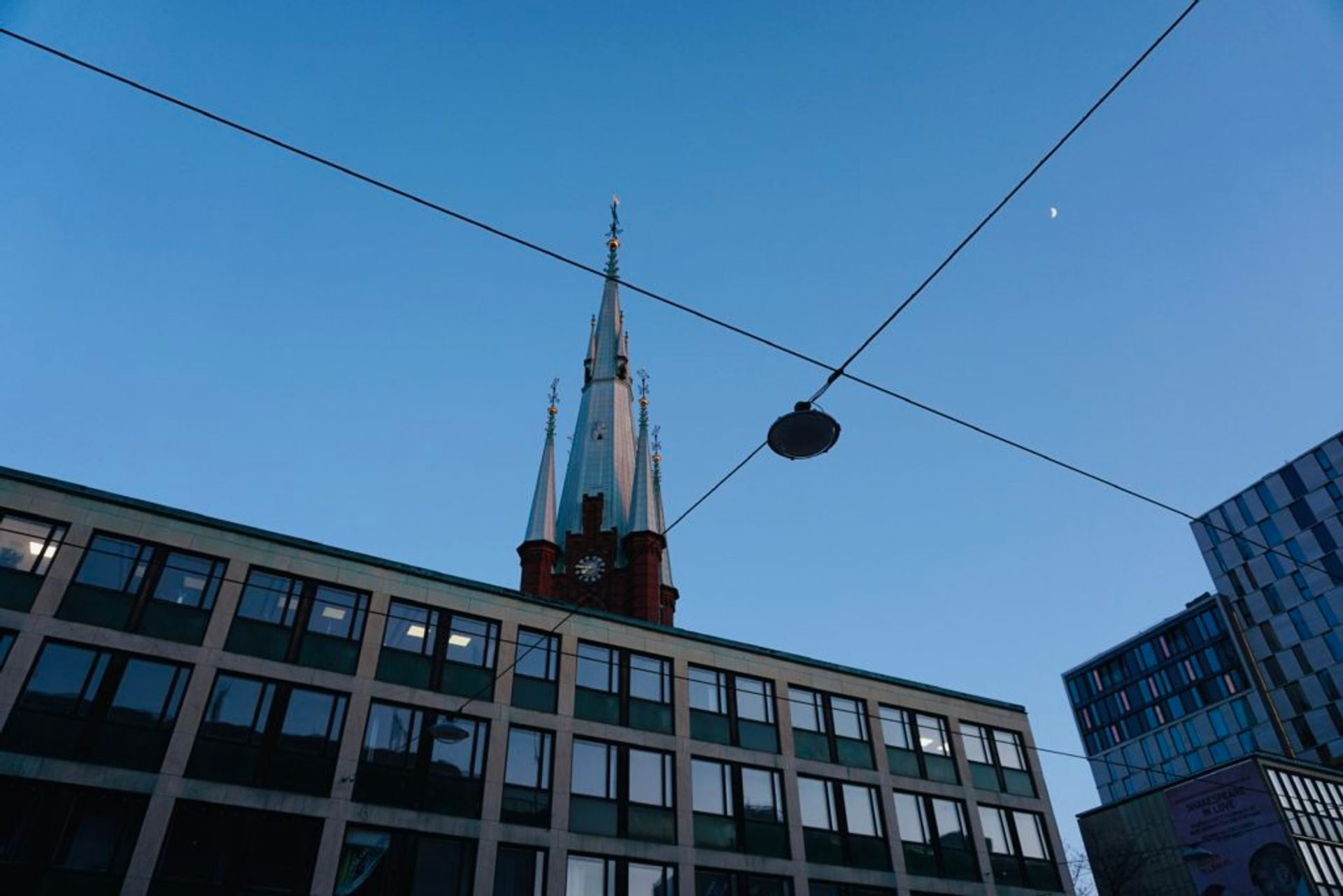 A church spire towers abover an office building.