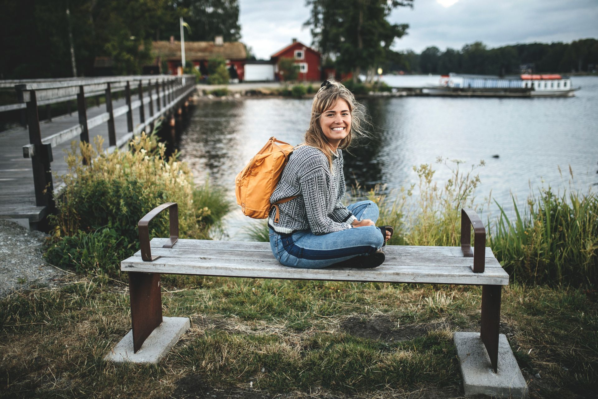 Woman sits on a bench in a park.