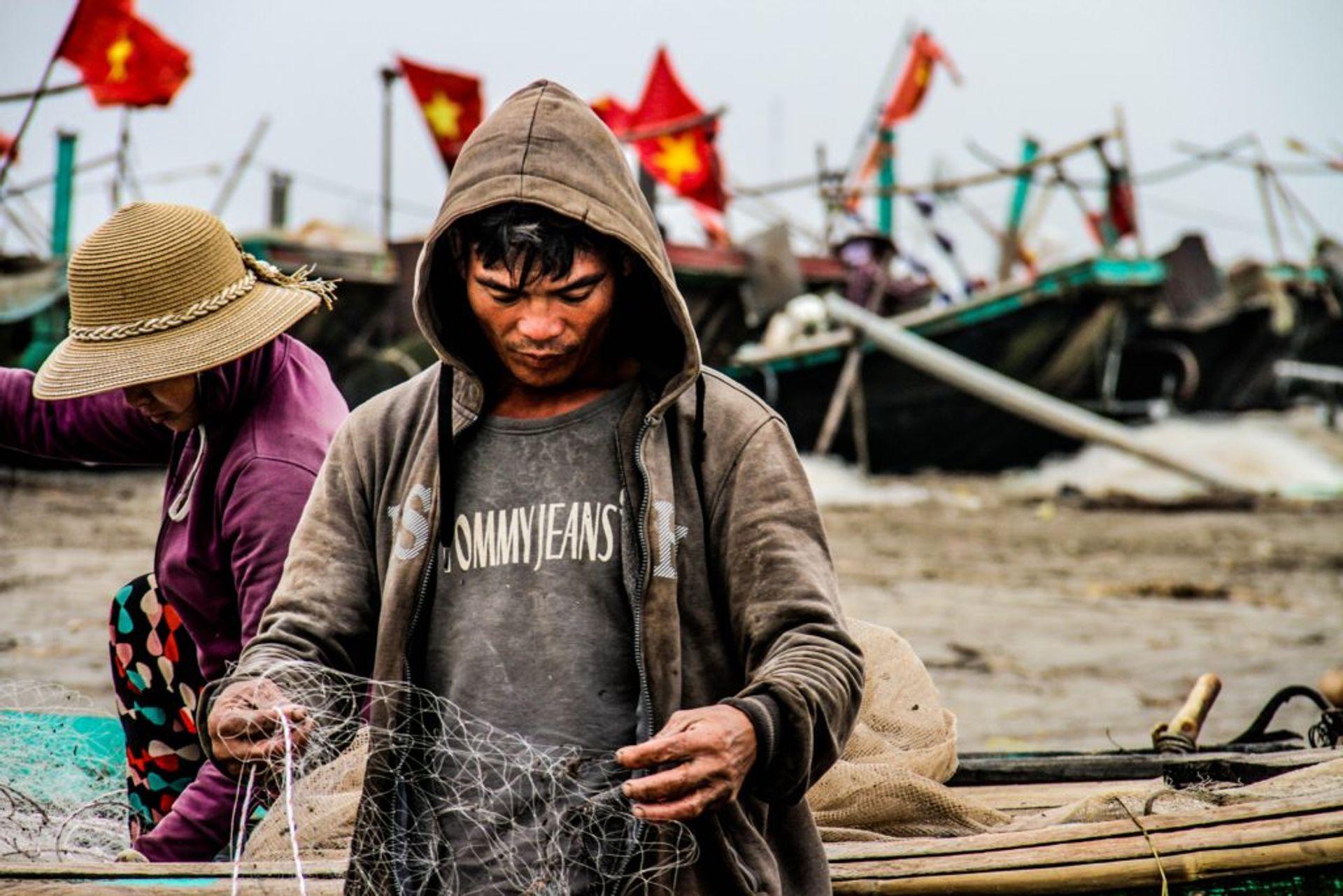 A fisherman looking at a fishing net.