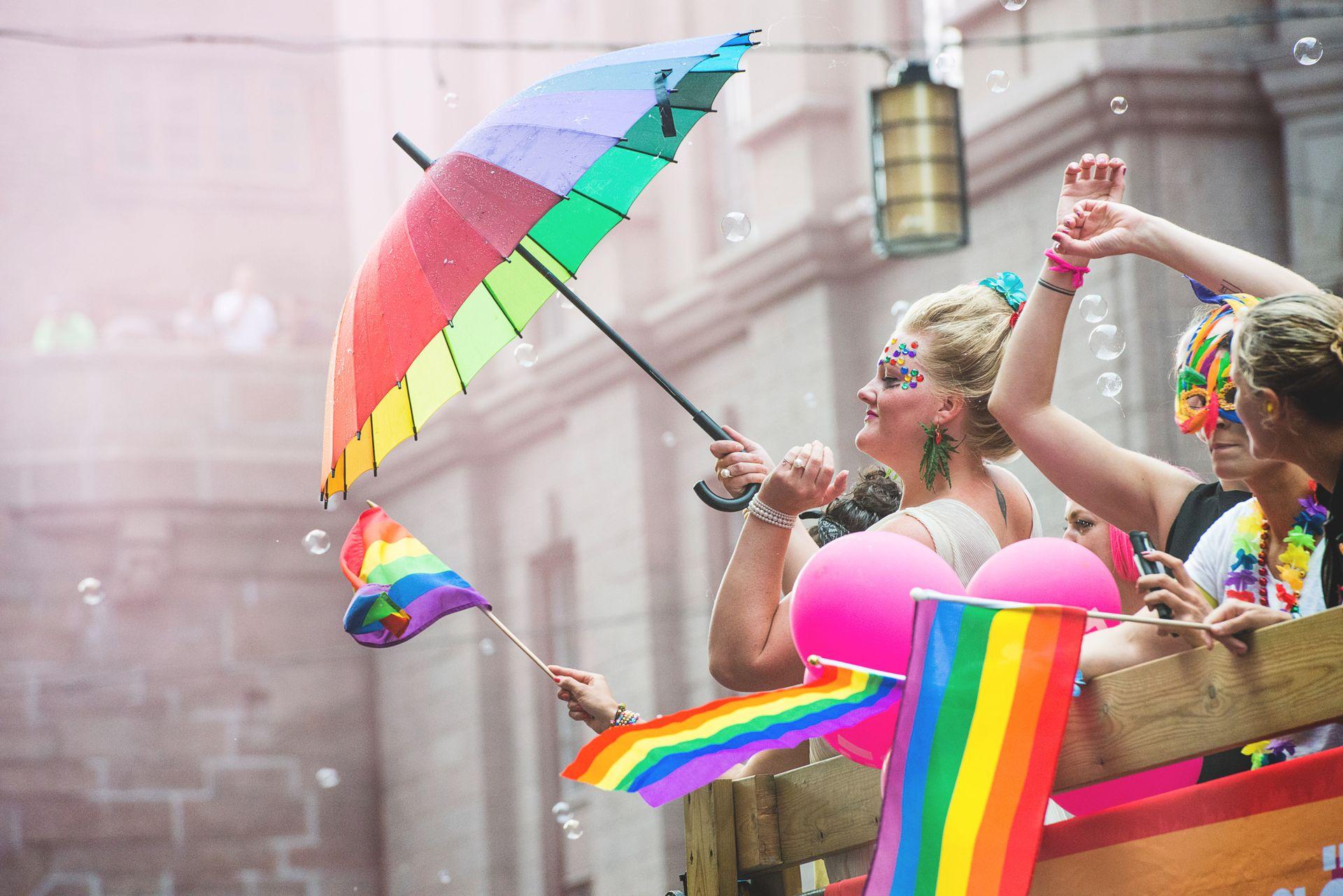 People waving rainbow flags at a Pride parade.