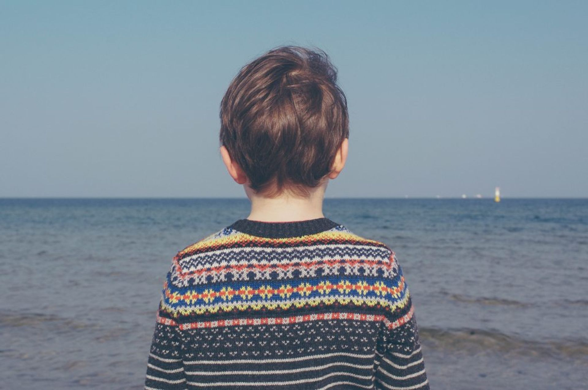 Close-up of a child looking at the ocean.