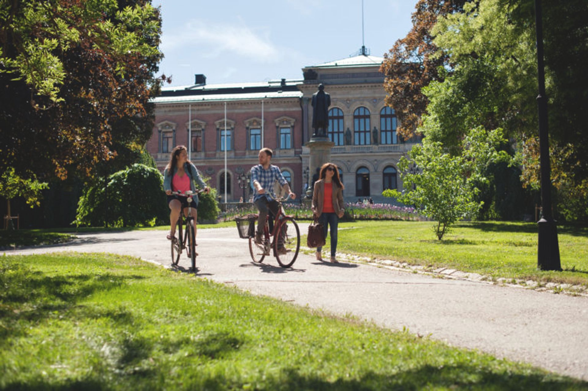 Students cycling in front of a large university building.