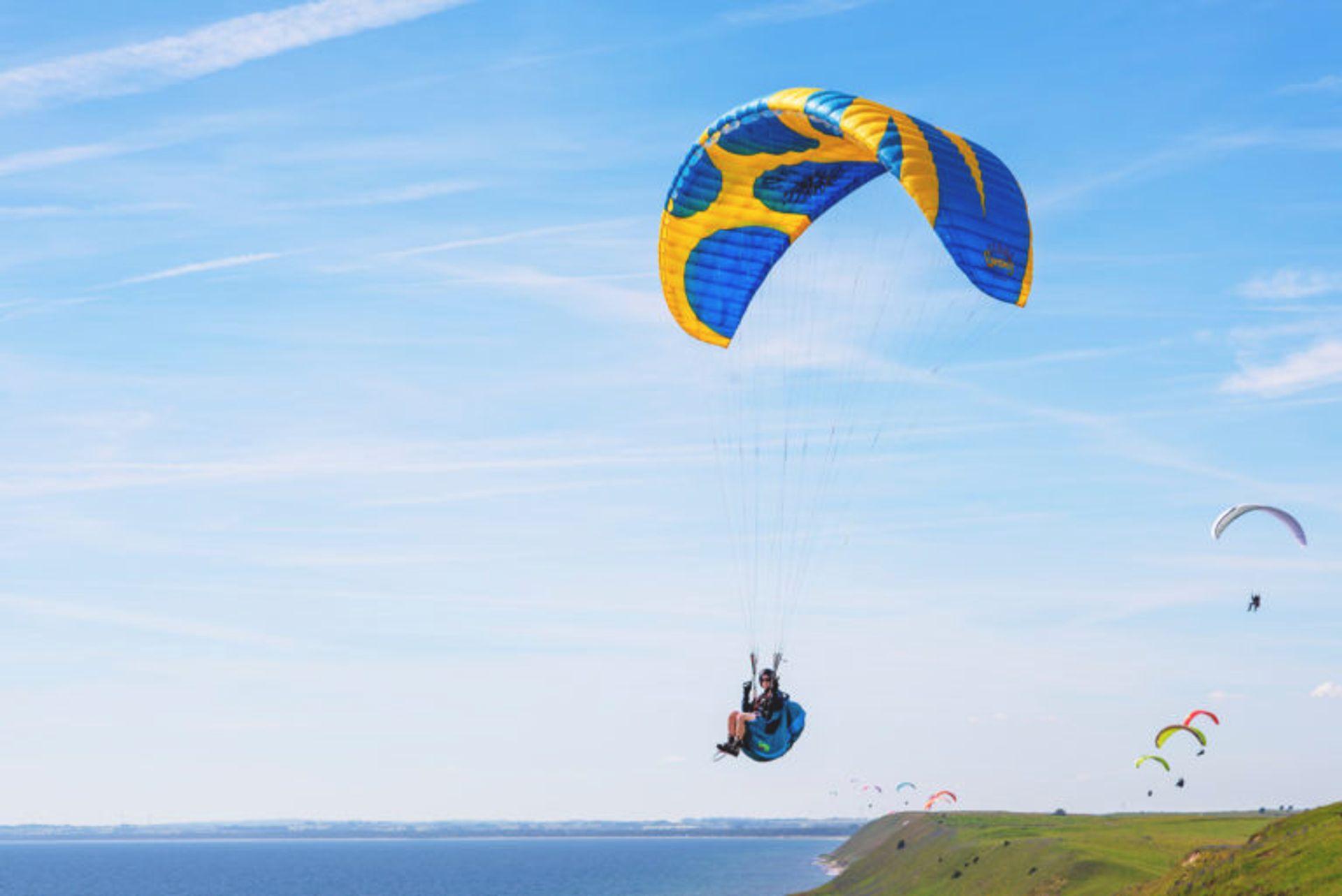A person hanggliding off a cliff.