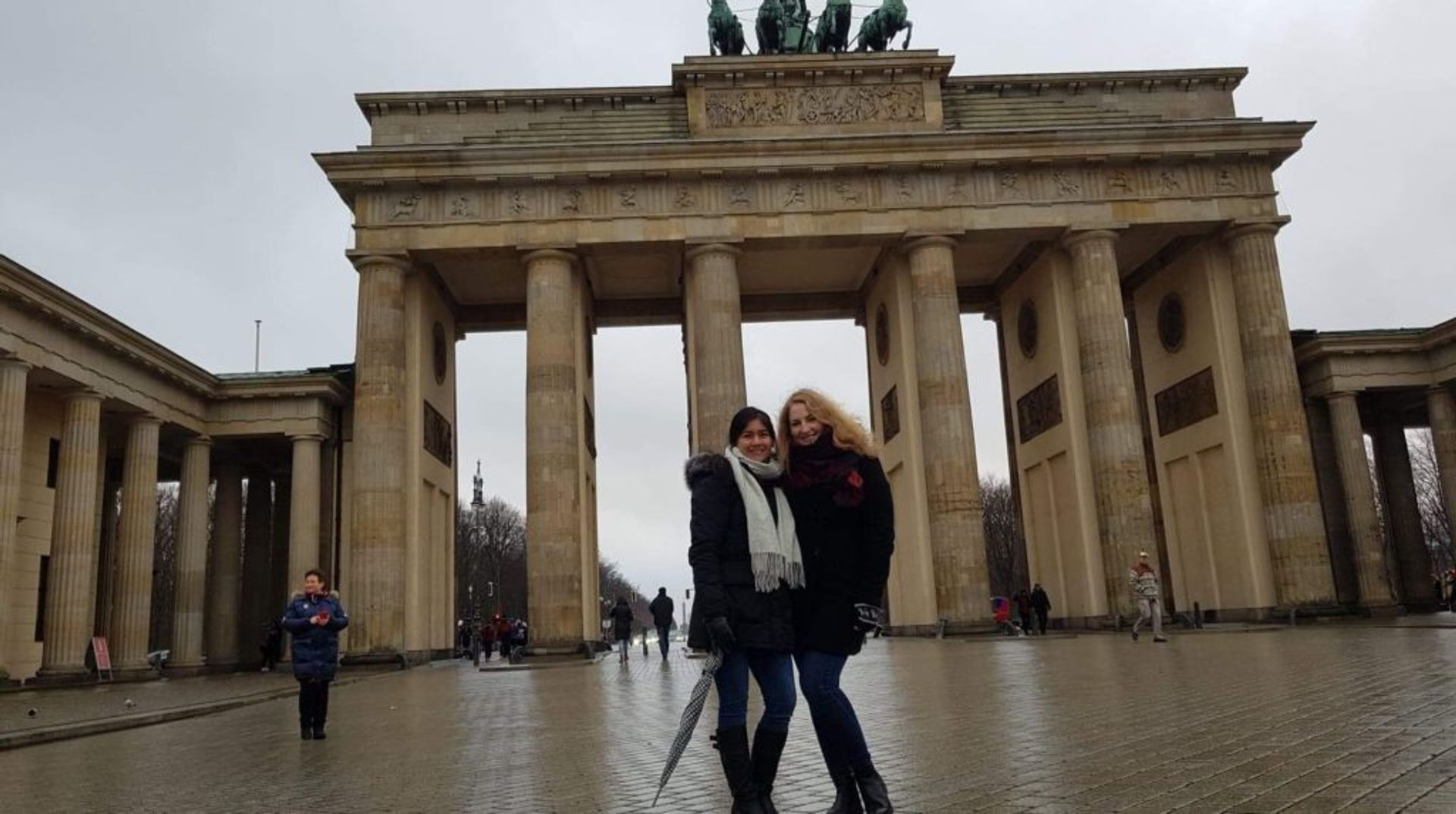 Two students posing for a photo in front of the Brandenburg Gate in Berlin.