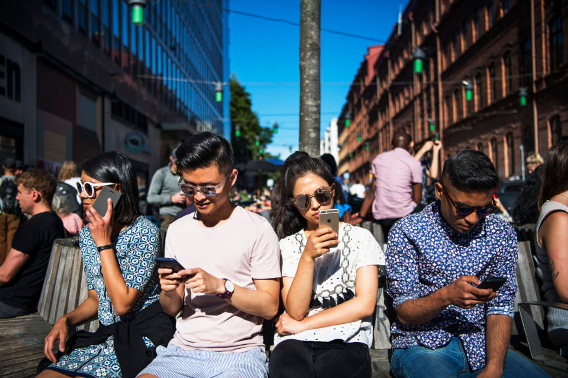 Four students sit together in a line, all looking at their mobile phones.