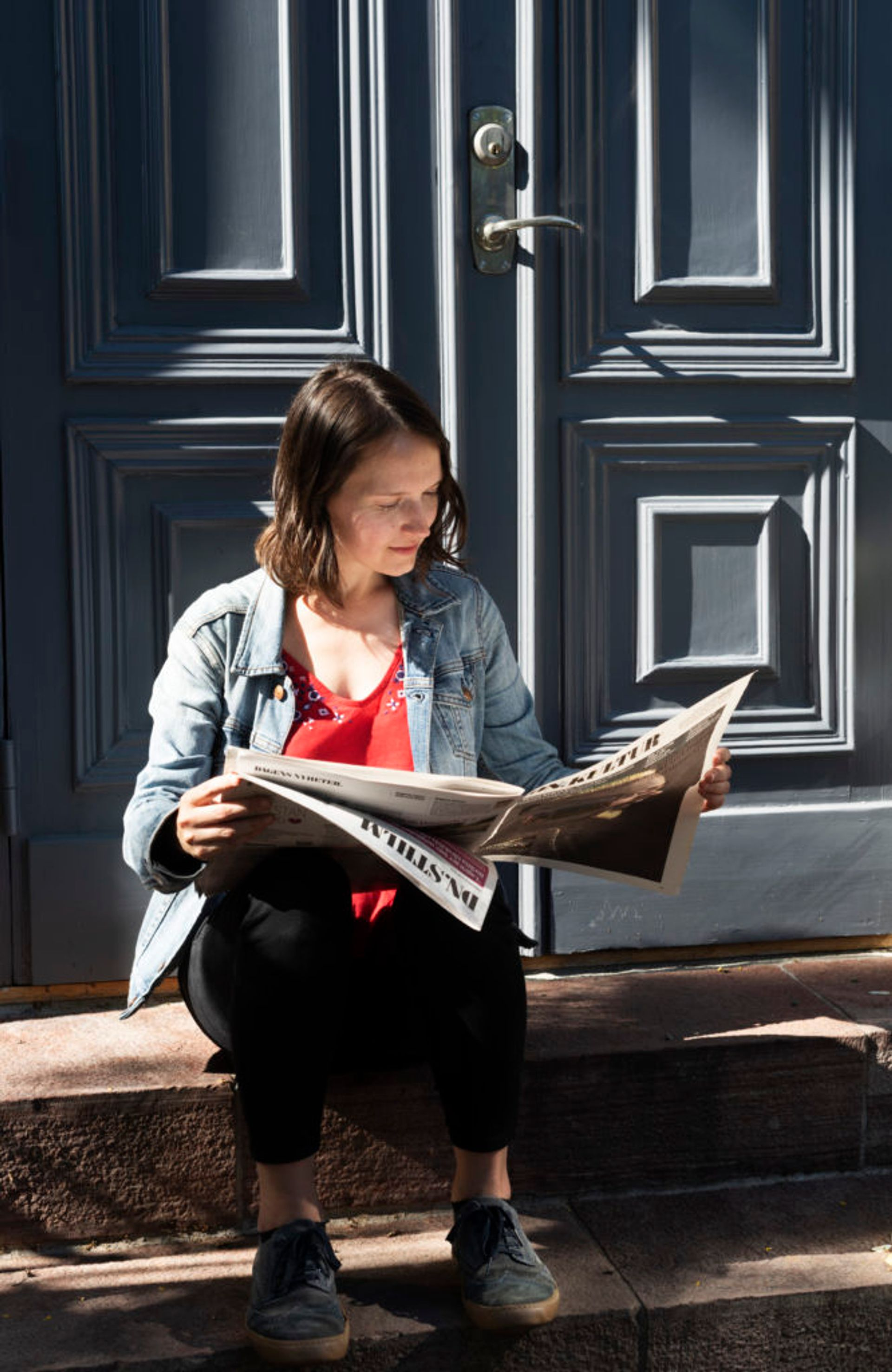 A student sitting on doorstep, reading a newspaper.