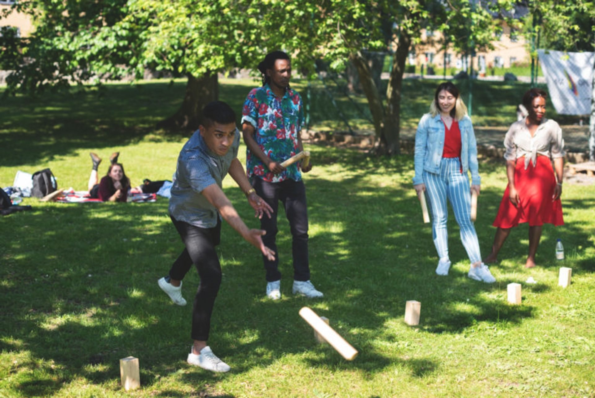 Students playing the Swedish game 'Kubb' in a park.