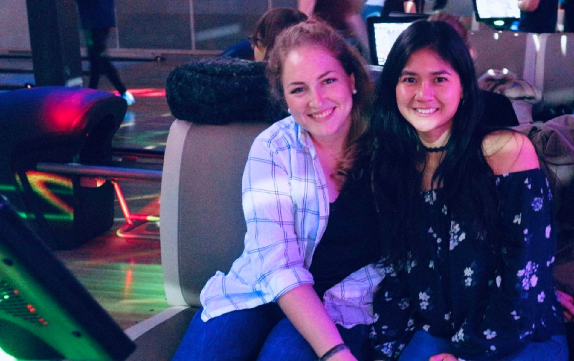 Two students sit together in a bowling hall.