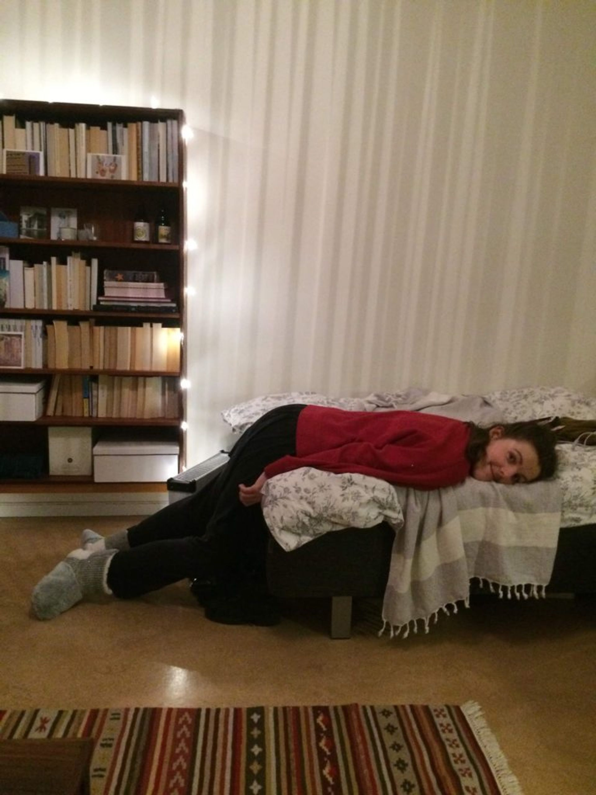 A student lying on a bed.