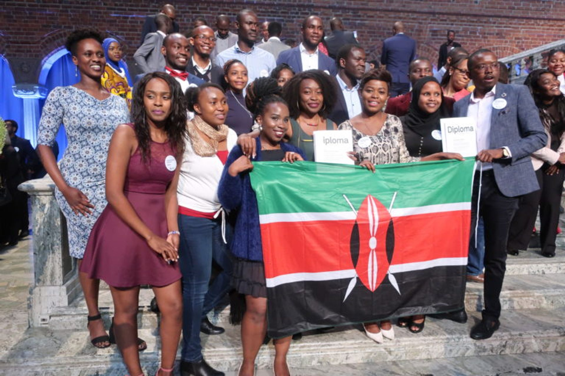 A group of students holding up a Kenyan flag.