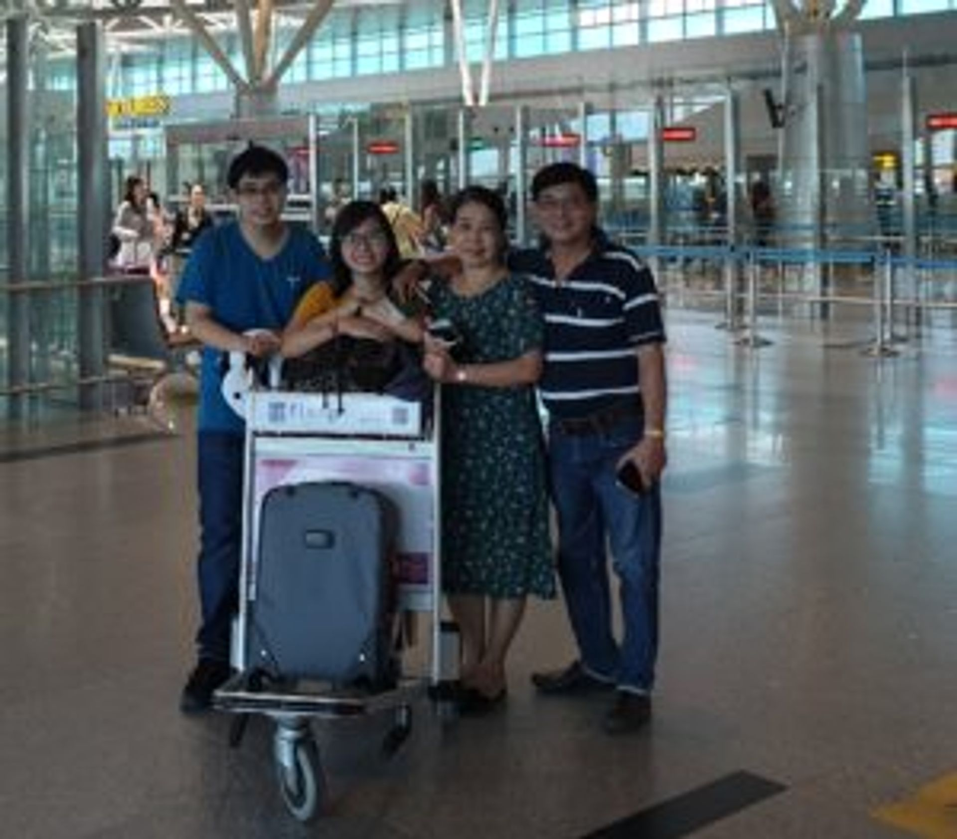 A family posing for a photo in an airport.