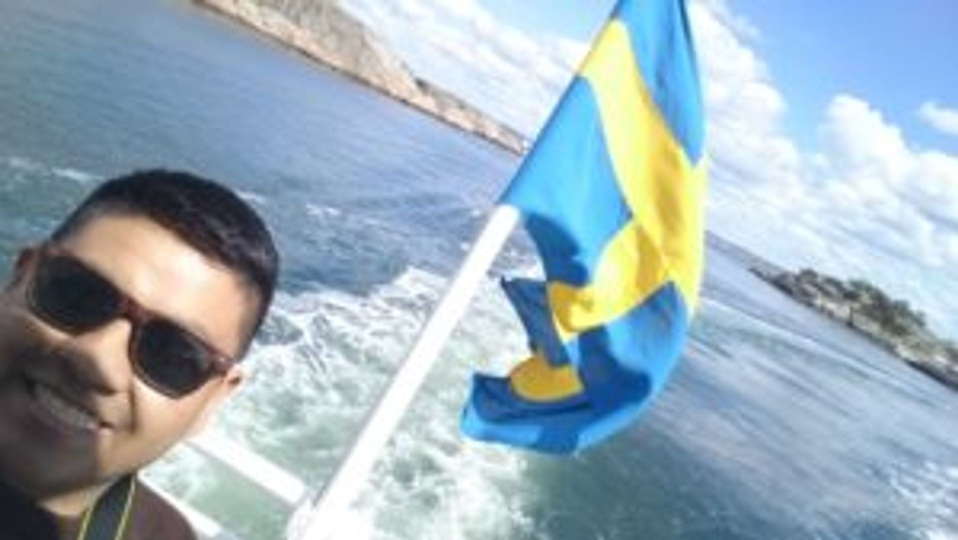 Student on a boat standing beside a Swedish flag.