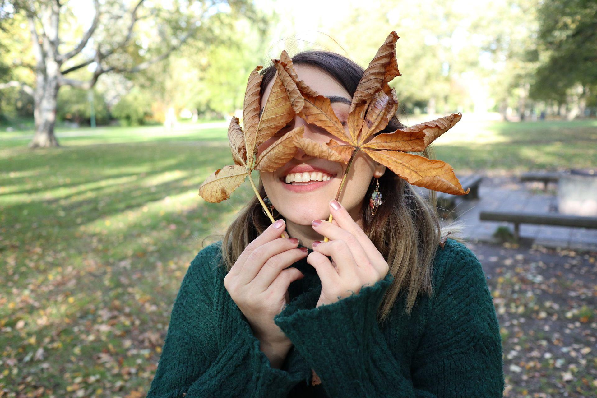 Student holds up orange leaves.