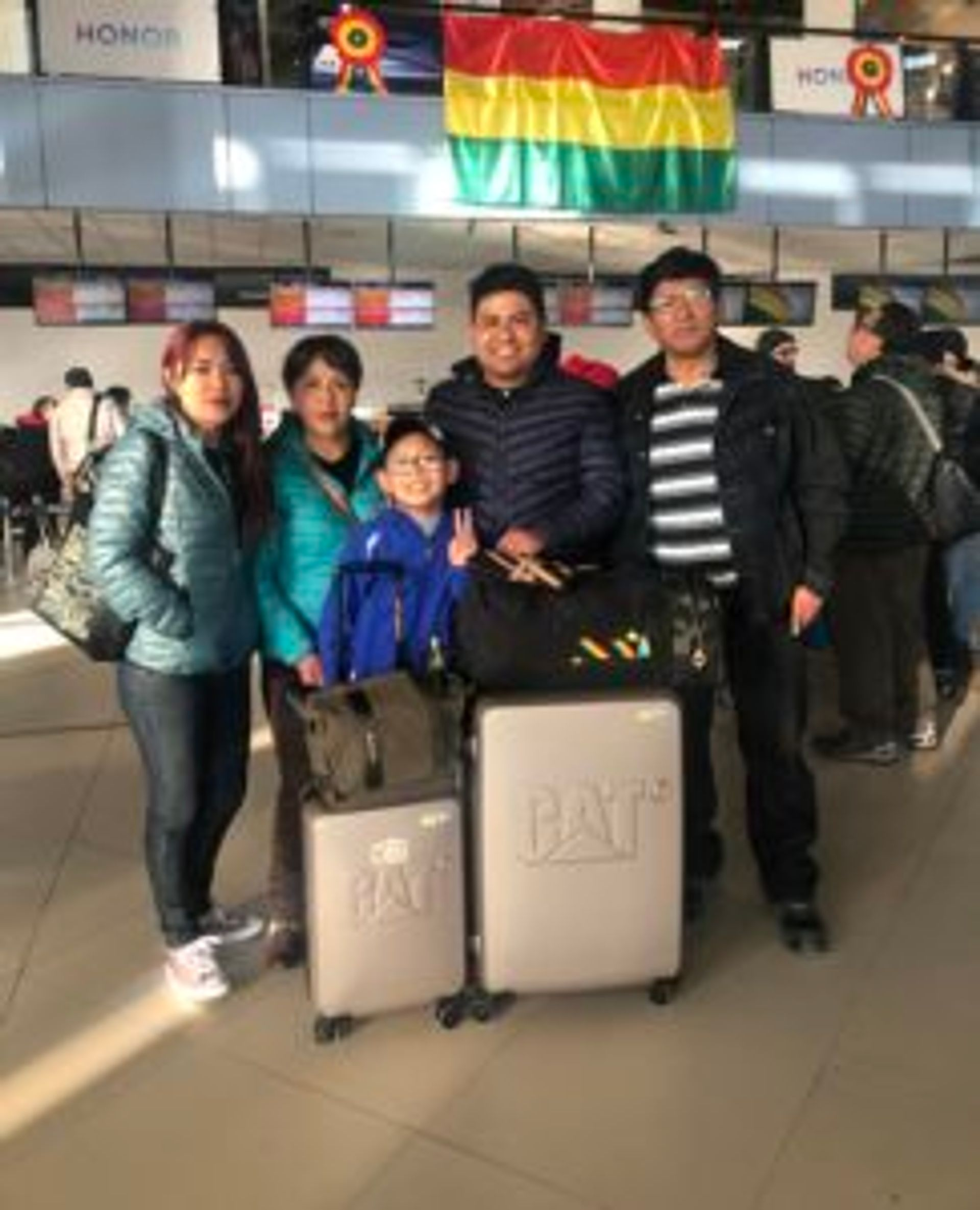A family poses for a photo at an airport.