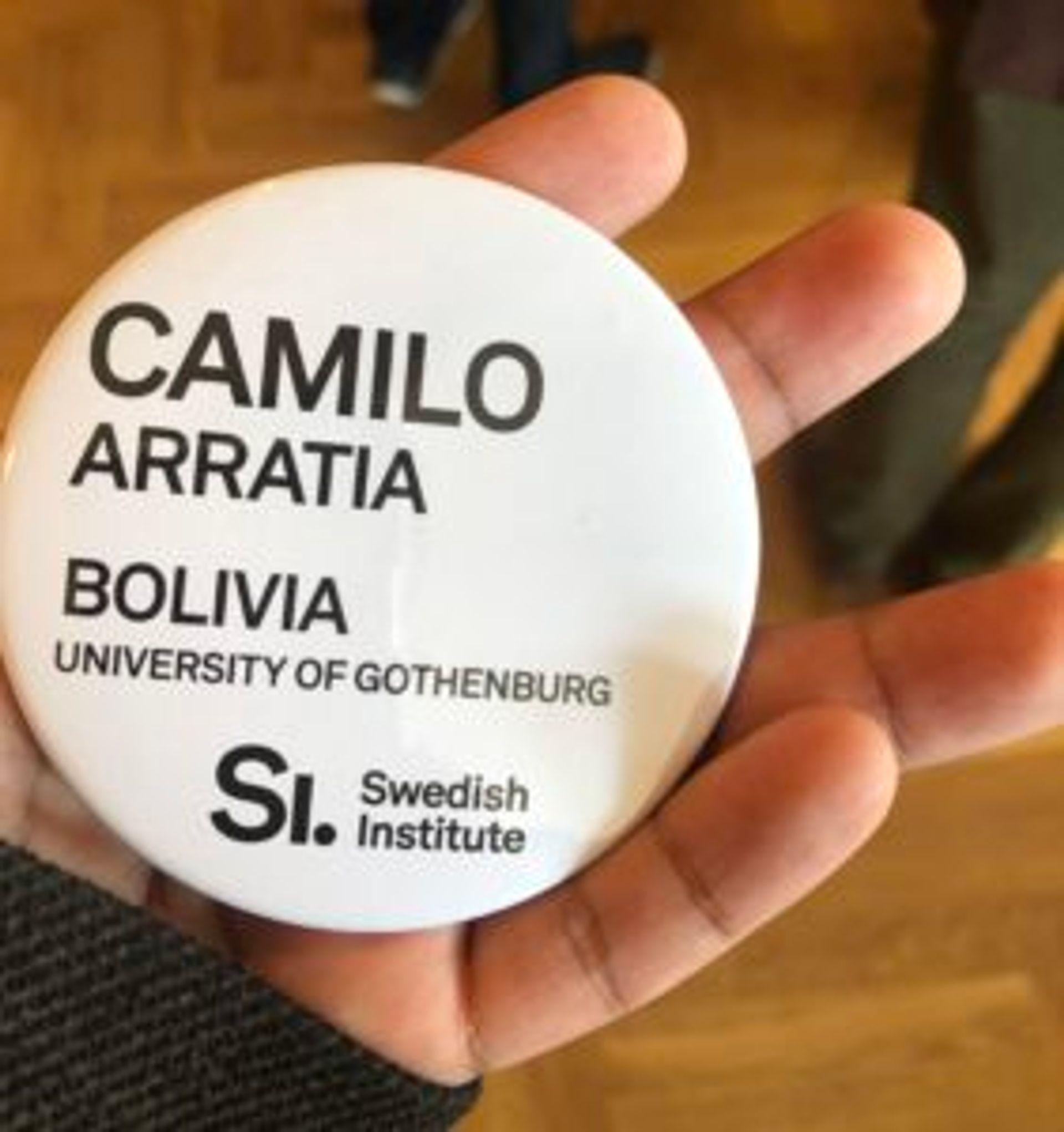 A white, round badge with the text 'Camilo Arratia. Bolivia. University of Gothenburg.' on it.