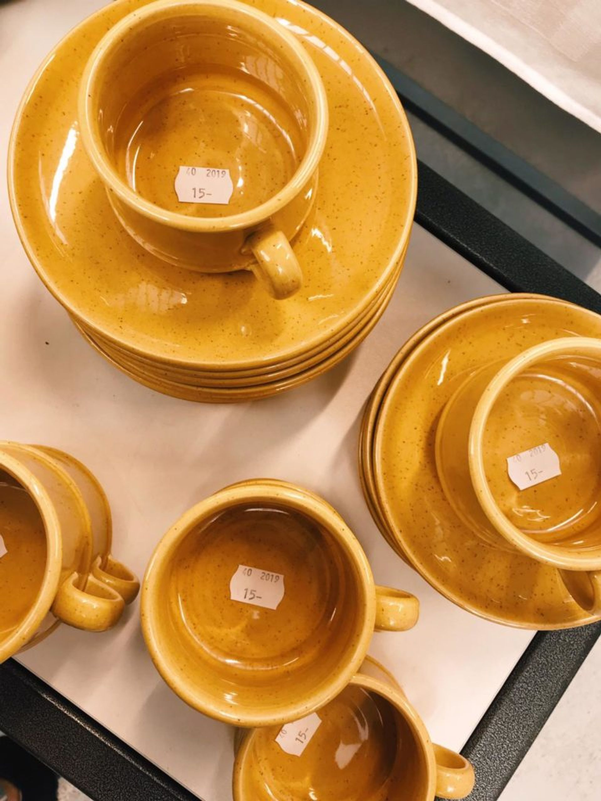 Close-up of mustard yellow cups and saucers.