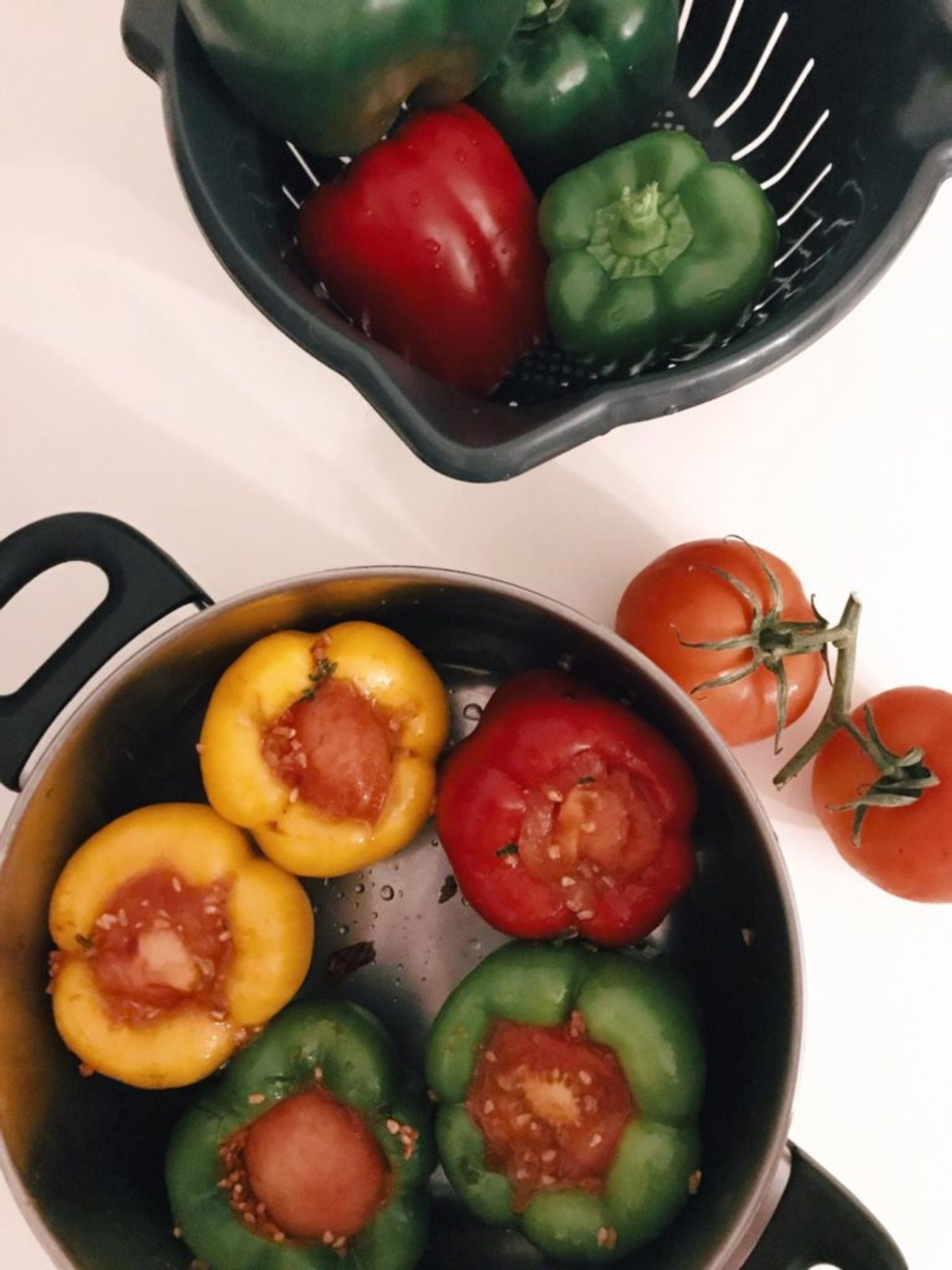 Close-up of peppers and tomatoes cooking in a pan.