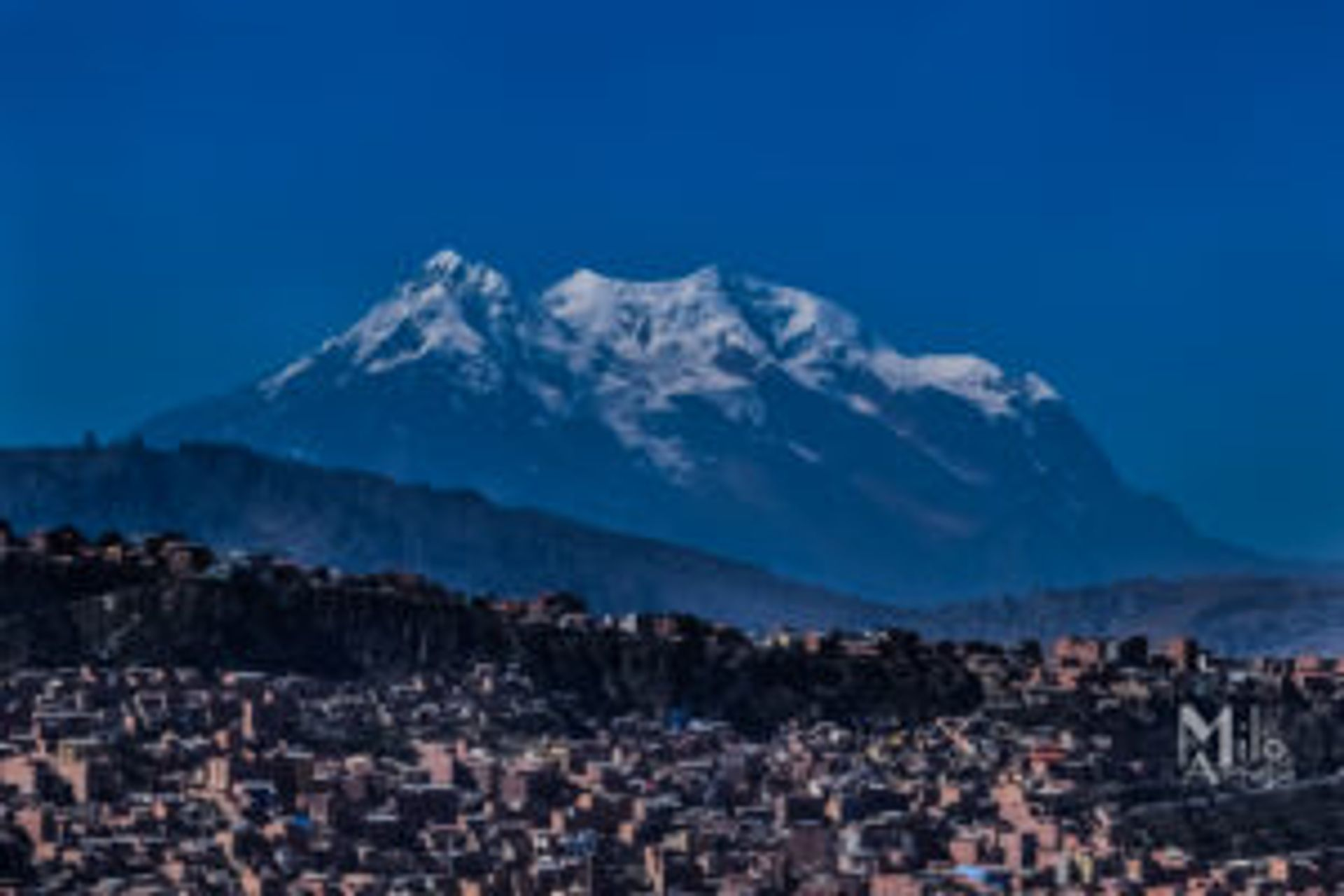 A snow-covered mountain above a large city.