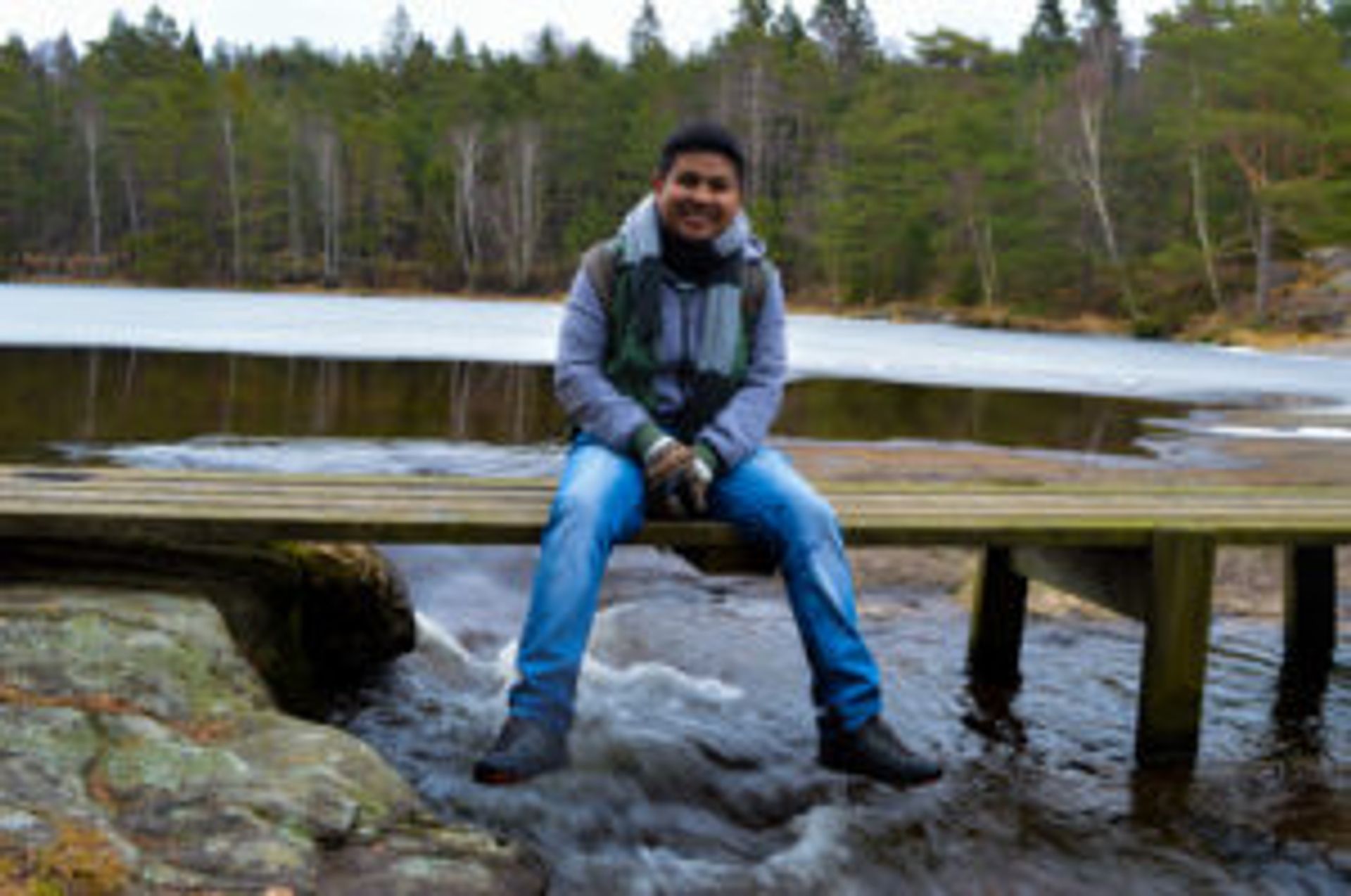 Camilo sitting on a small, wooden footbridge by a lake outside of Gothenburg.