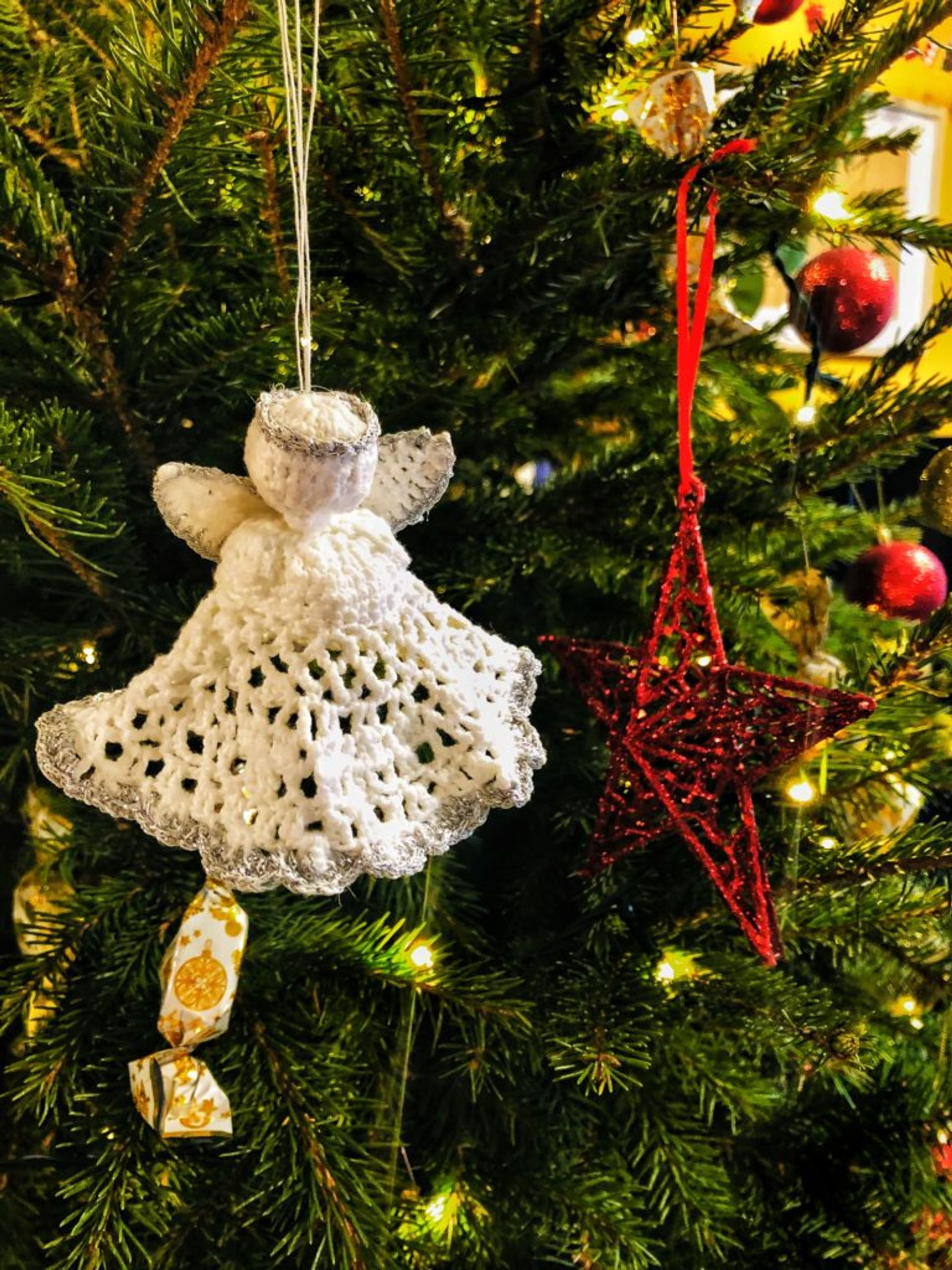 A crochet angel decoration hanging on a Christmas tree.