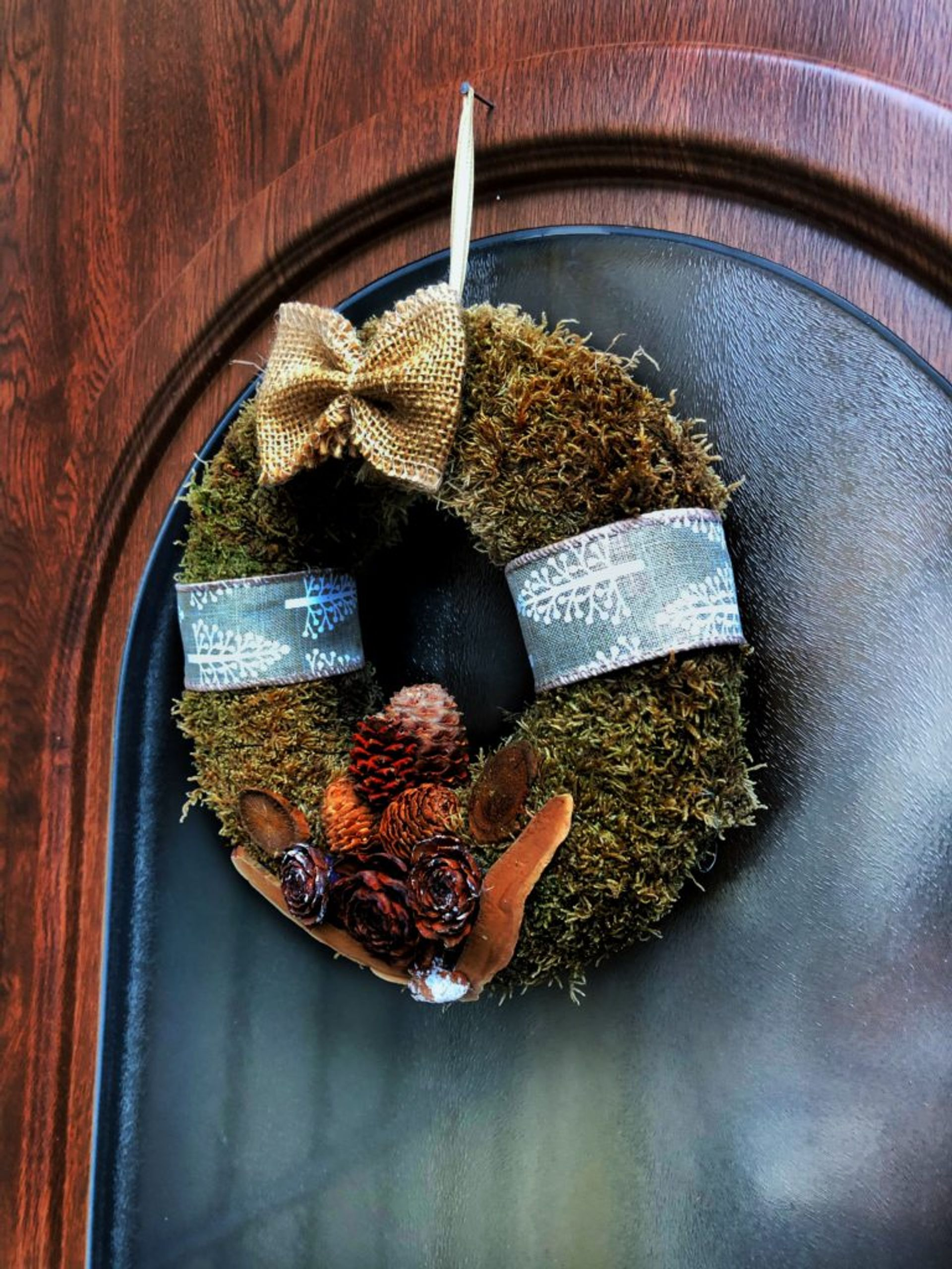 A Christmas wreath hanging on a door.