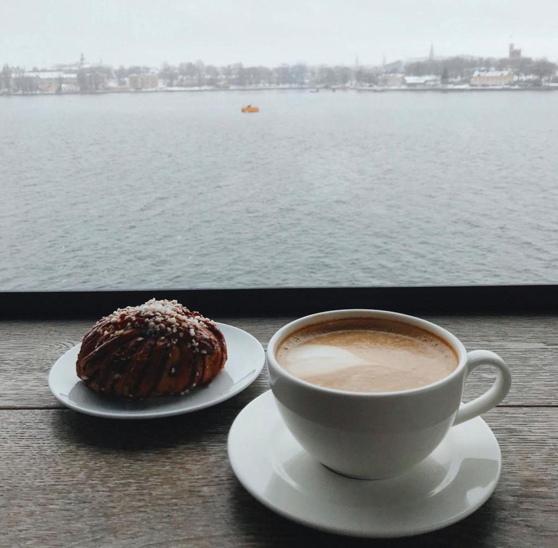 A cinnamon bun and cup of coffee.