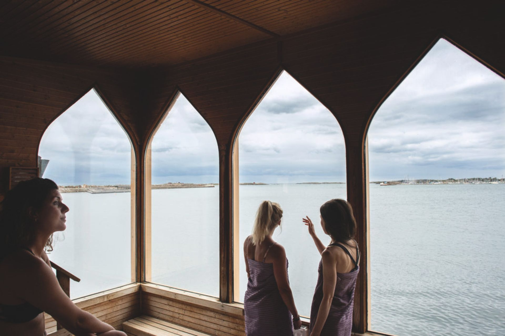 People in a sauna, looking out of the window.