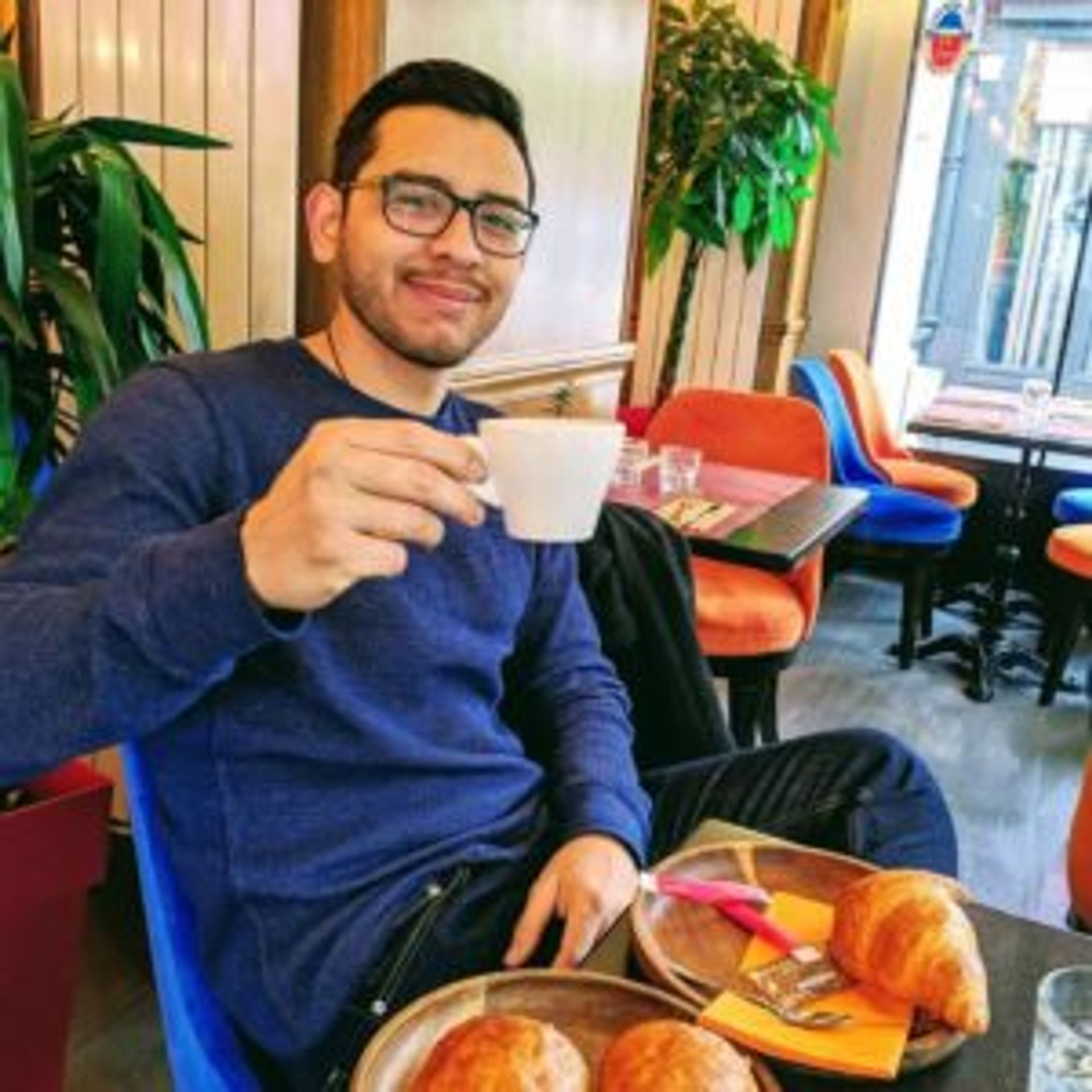Sergio drinking coffee and pastries in a cafe.