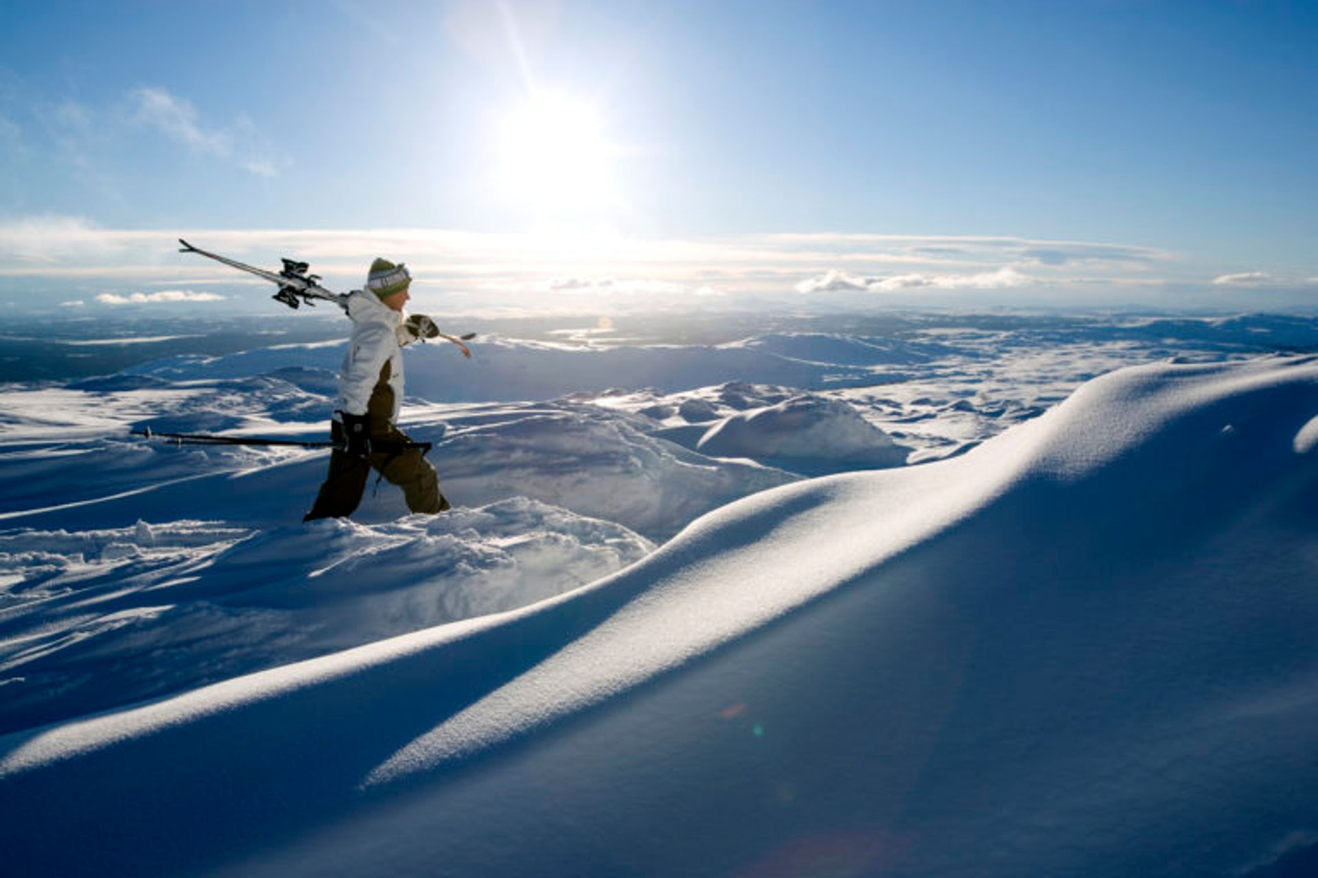 A person walking with skis on a snowy mountain.
