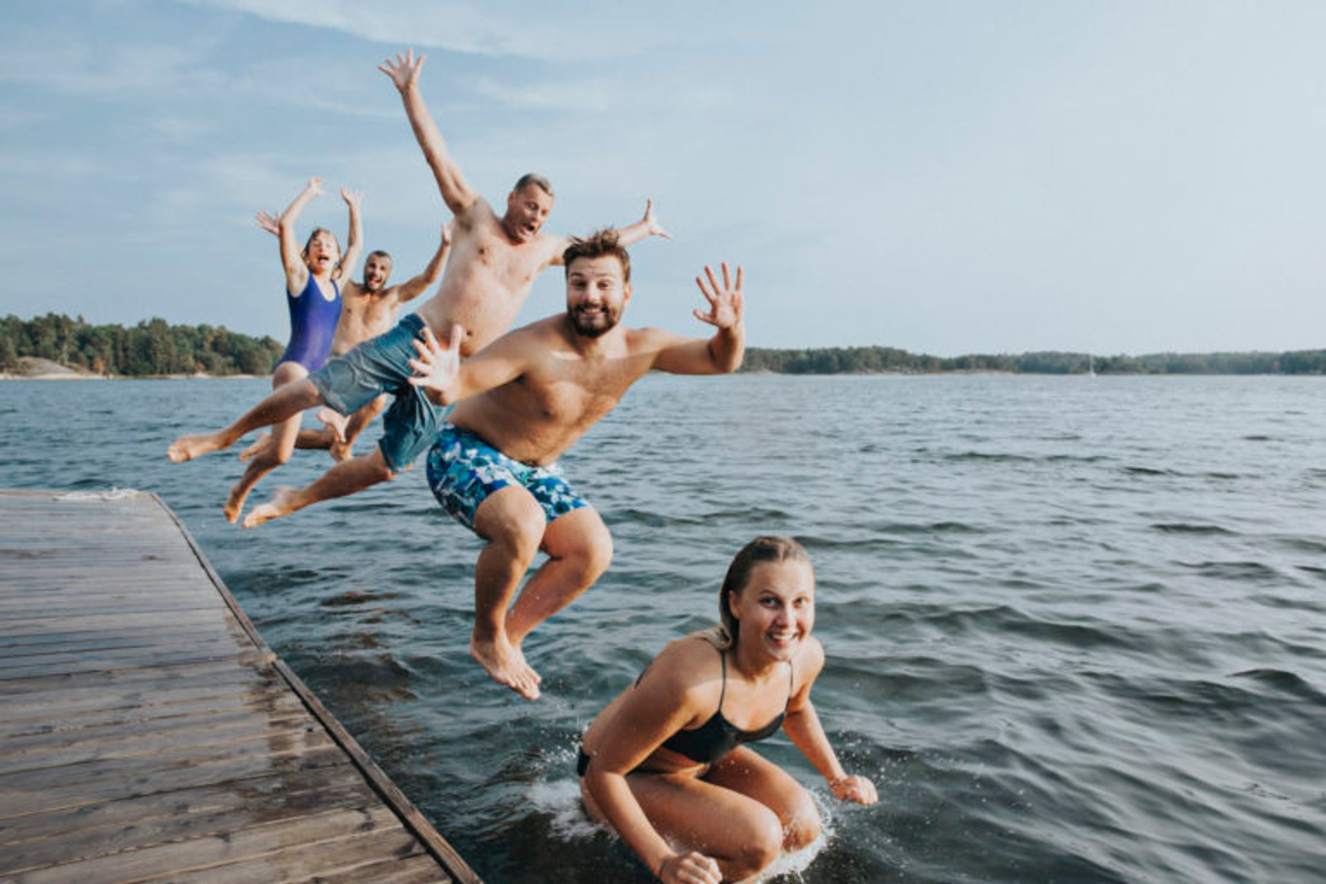 People jumping into a lake from a wooden jetty.