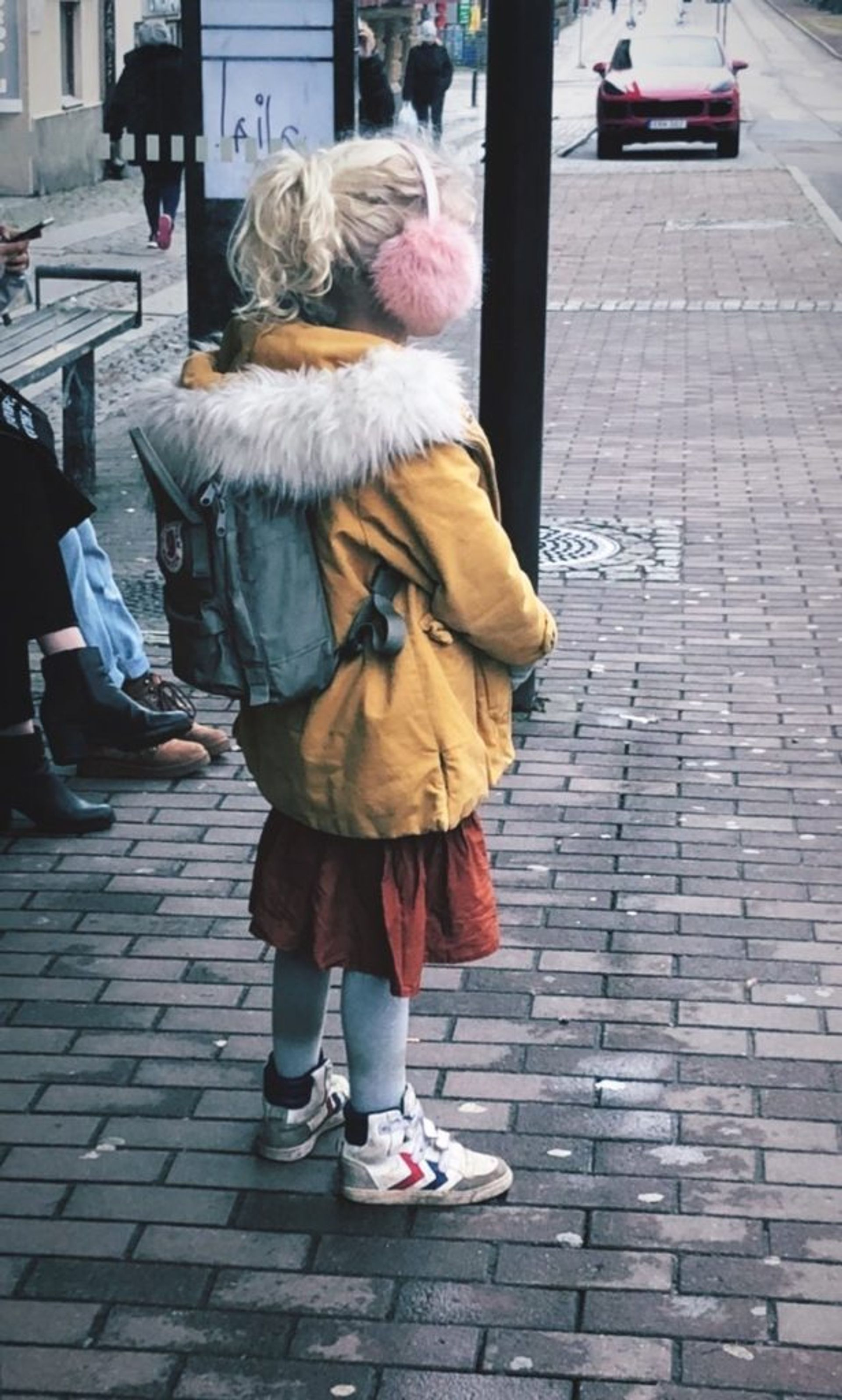 A child standing at a bus stop.