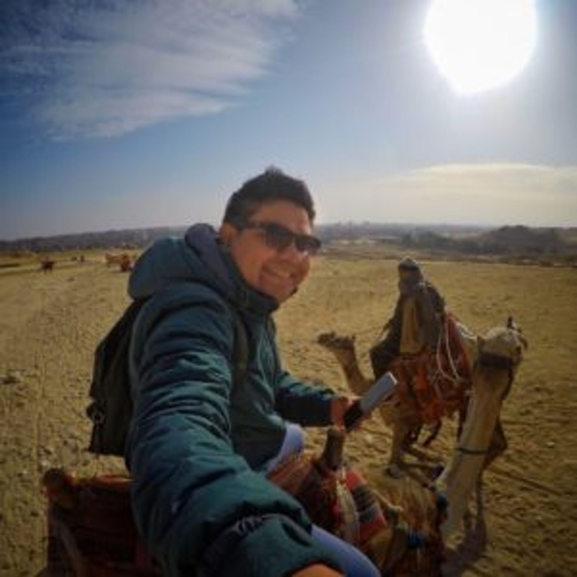 Camilo taking a selfie of himself sitting on a camel.