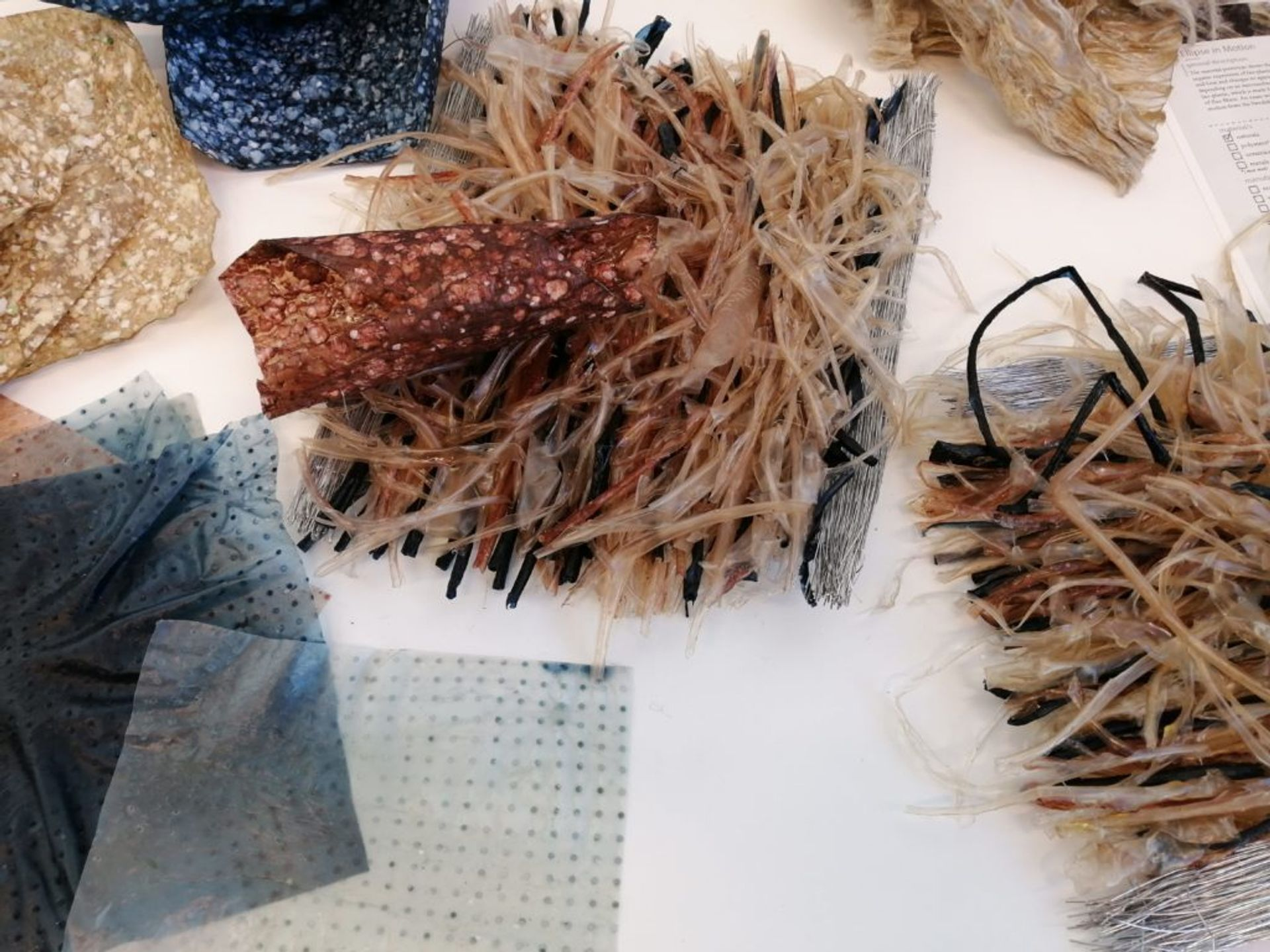 A selection of different textiles made from recycled paper and bio-plastic materials.