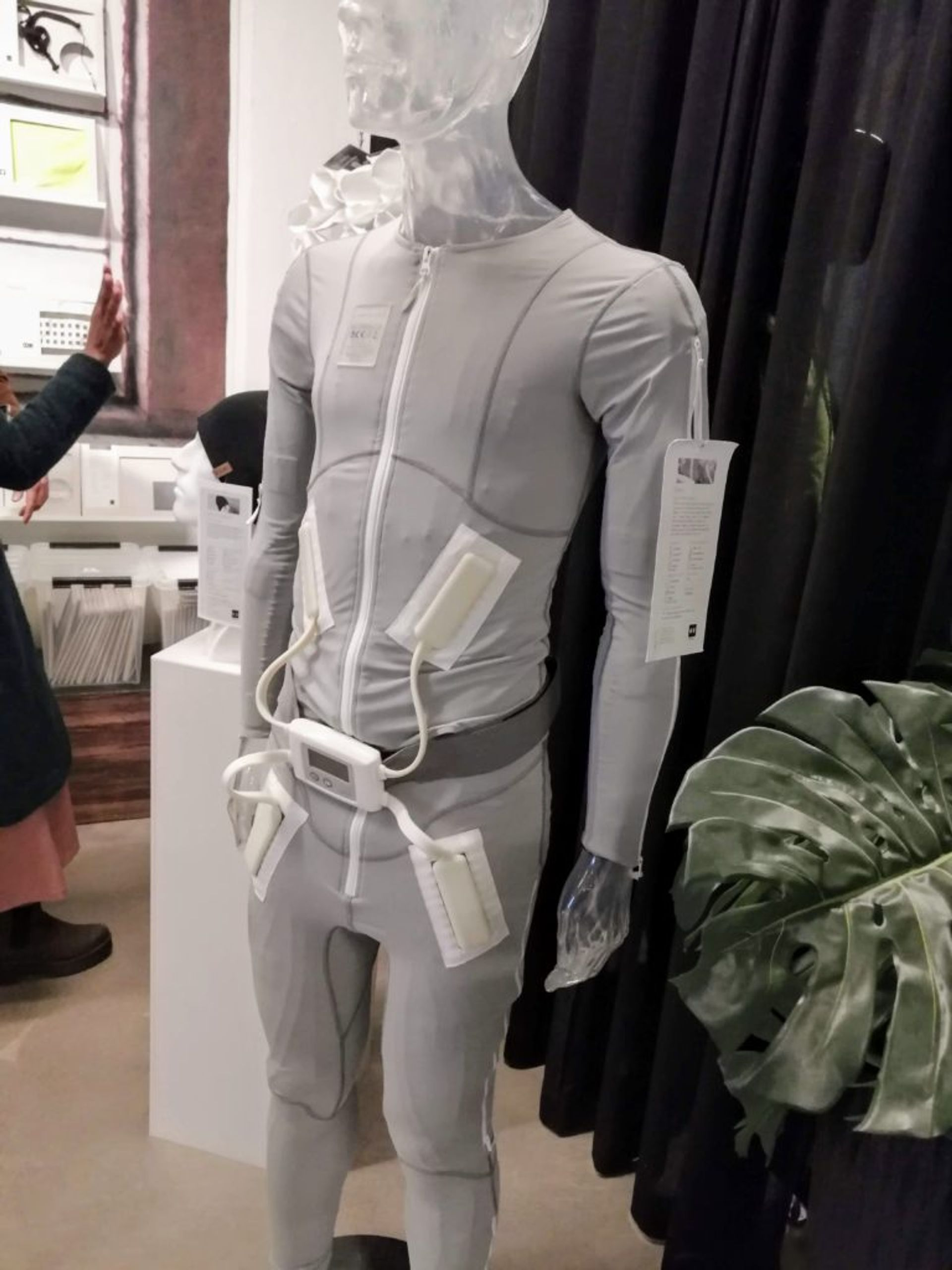 A grey bodysuit on a mannequin with electrical currents attached.