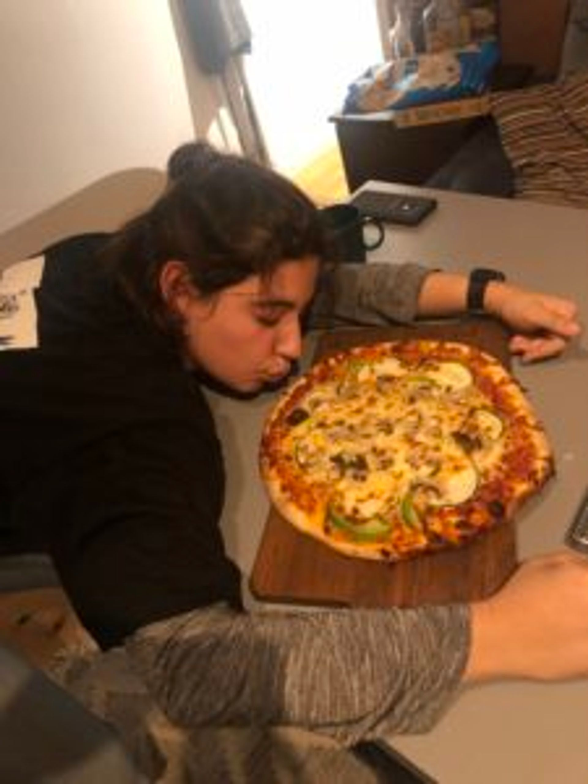 A person looking at a pizza.