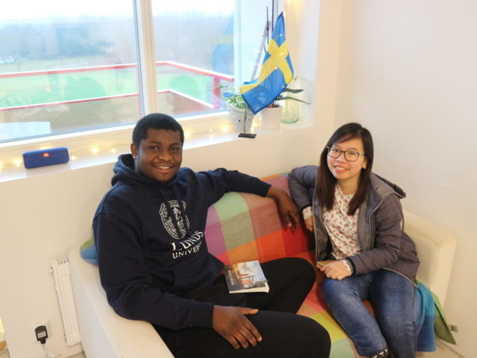 Two students sit on a sofa together.